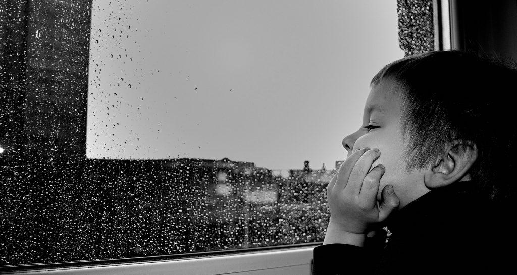 un bambino che guarda fuori dalla finestra mentre piove, foto in bianco e nero