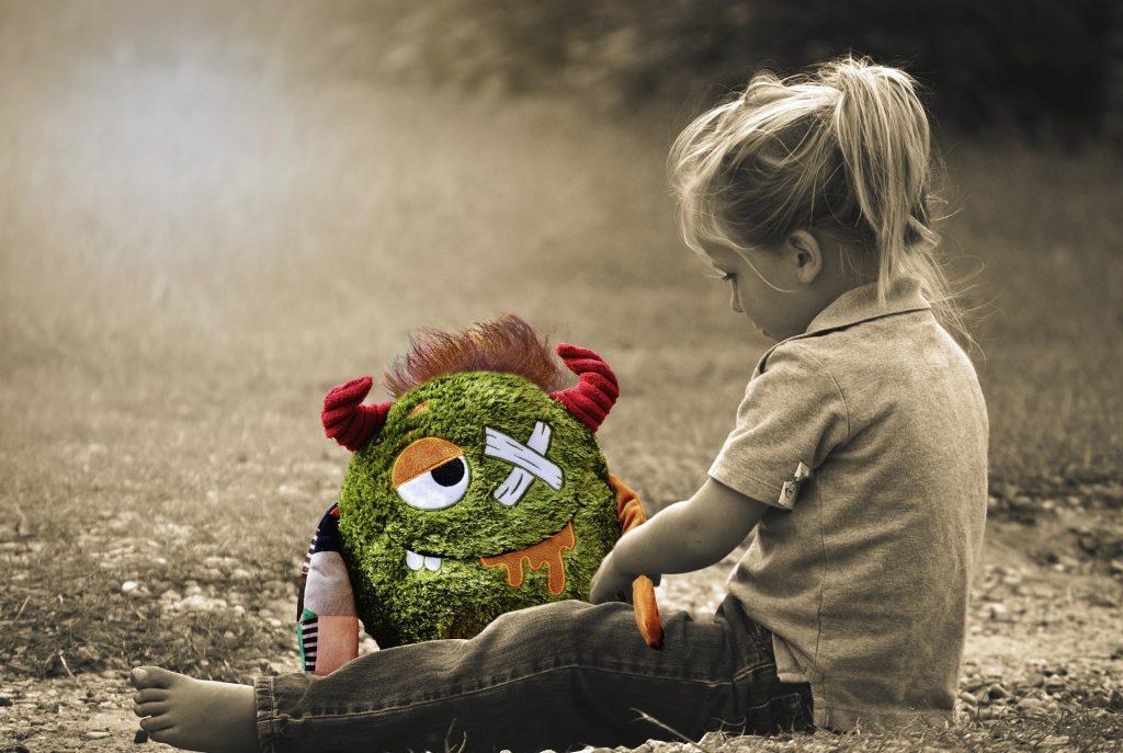 una bambina gioca con un pupazzo da curare