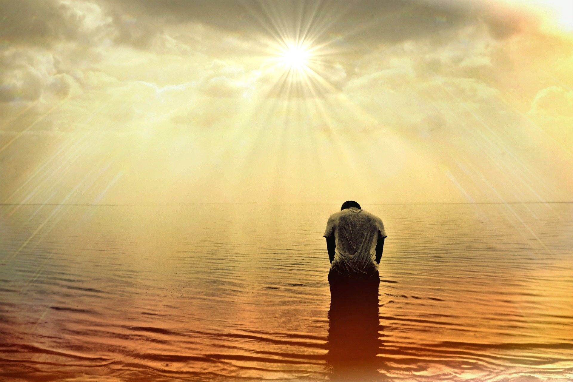 un uomo in piedi in mezzo al mare al tramonto ricurvo su se stesso