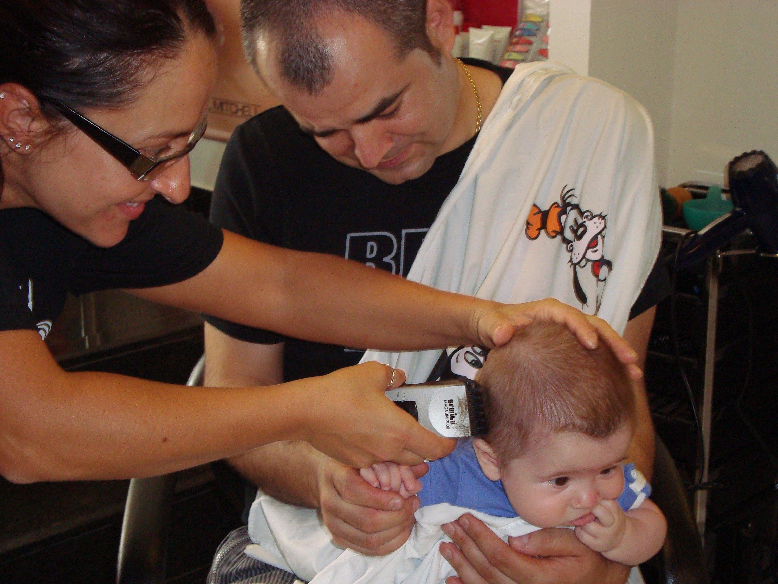 Giuliano a 6 mesi in braccio al babbo mentre la parrucchiera gli taglia i capelli