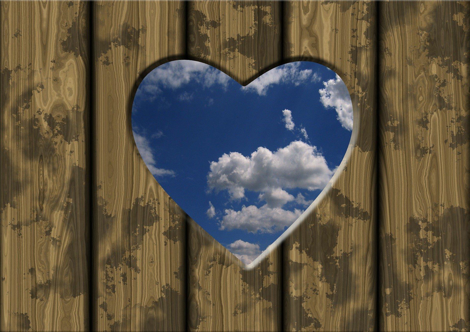 cuore inciso su una parete di tavole di legno dal quale si intravede il cielo blu con le nuvole