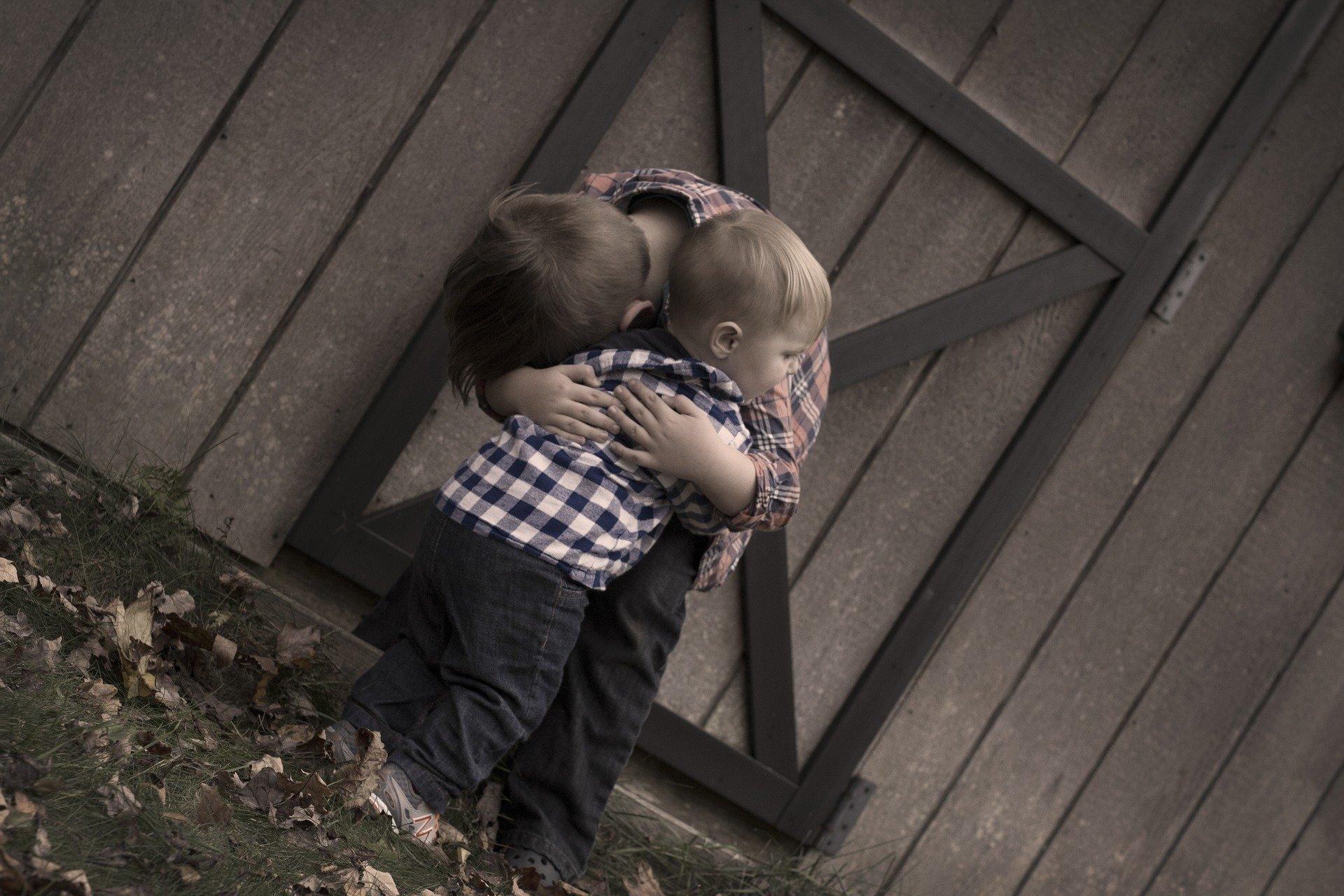un bambino abbraccia un altro bimbo più piccolo di lui
