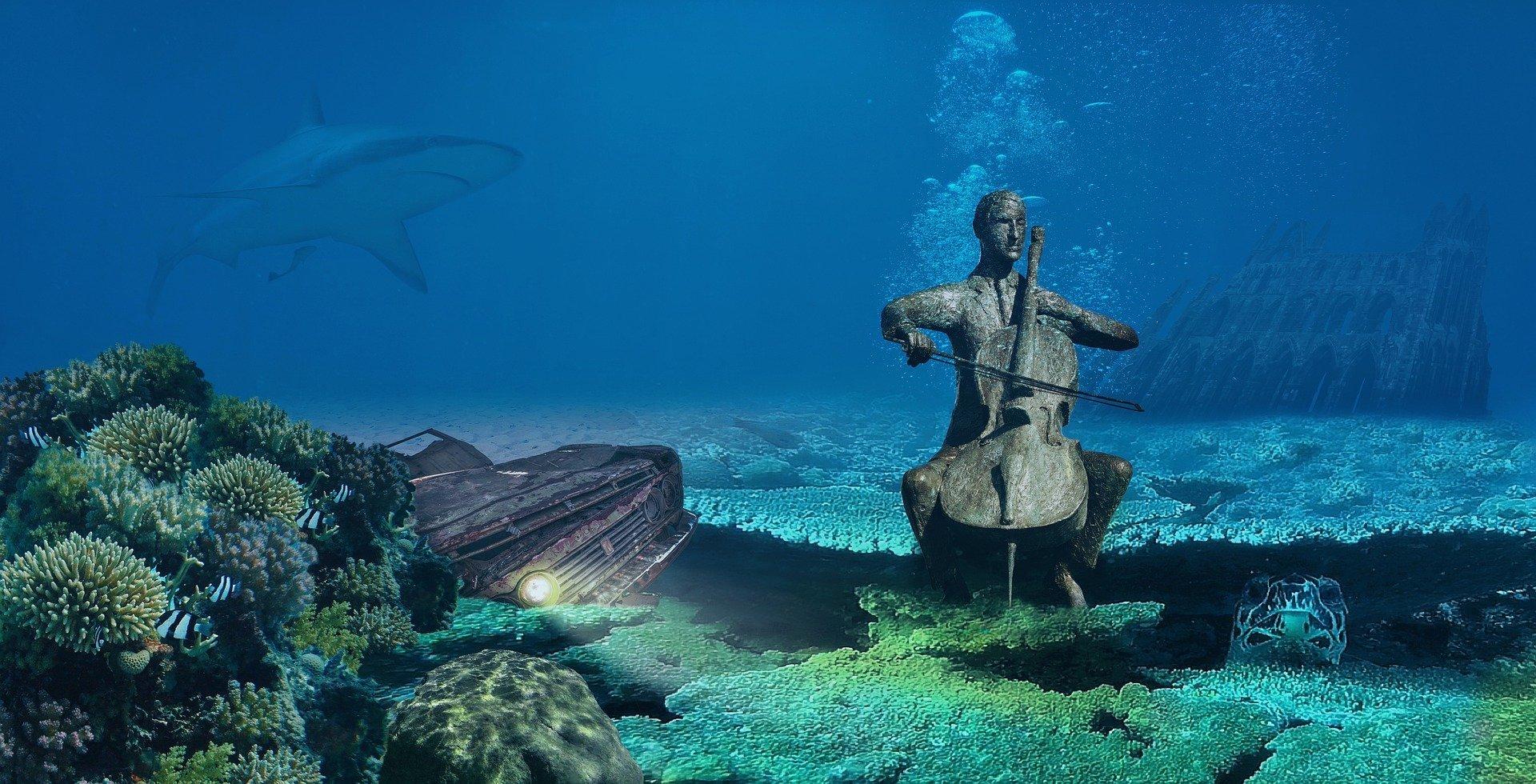 sul fondale del mare, la statua di un violoncellista che suona, un'auto arrugginita coi fari accesi, una cattedrale, una tartaruga gigante che esce dalle rocce e uno squalo che si sta avvicinando