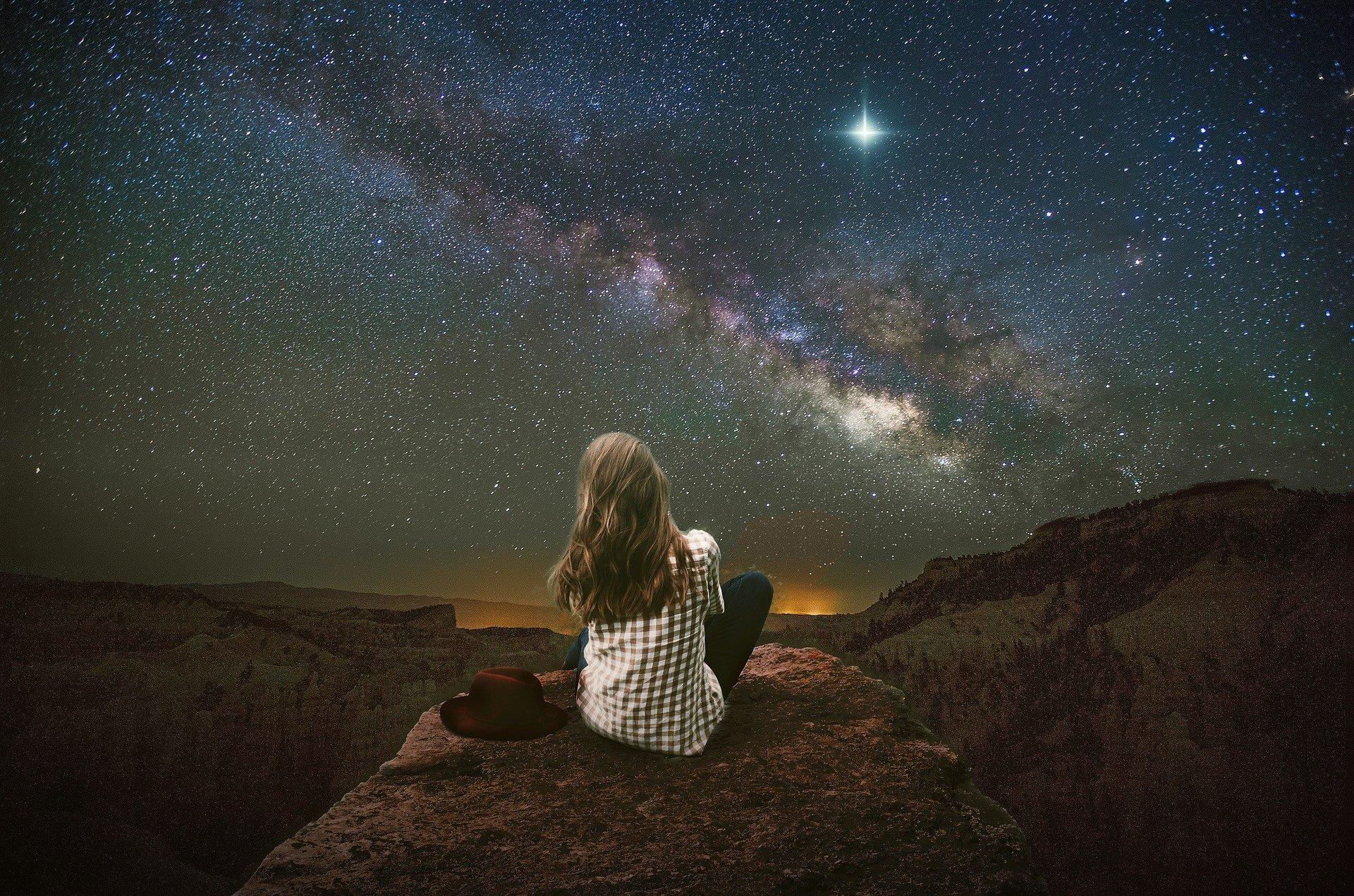 una ragazza di notte seduta su una roccia ad osservare la luna e le stelle