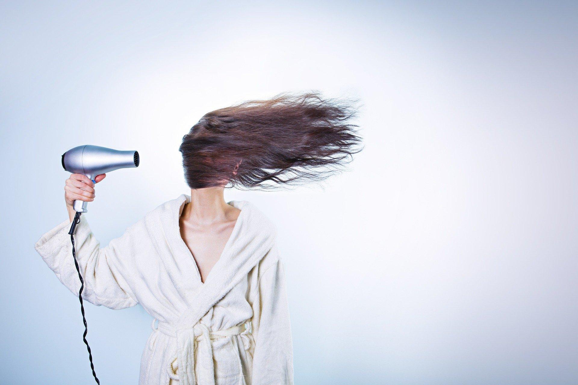 una donna in accappatoio con il phon accesso ed i capelli lunghi a coprirle il volto