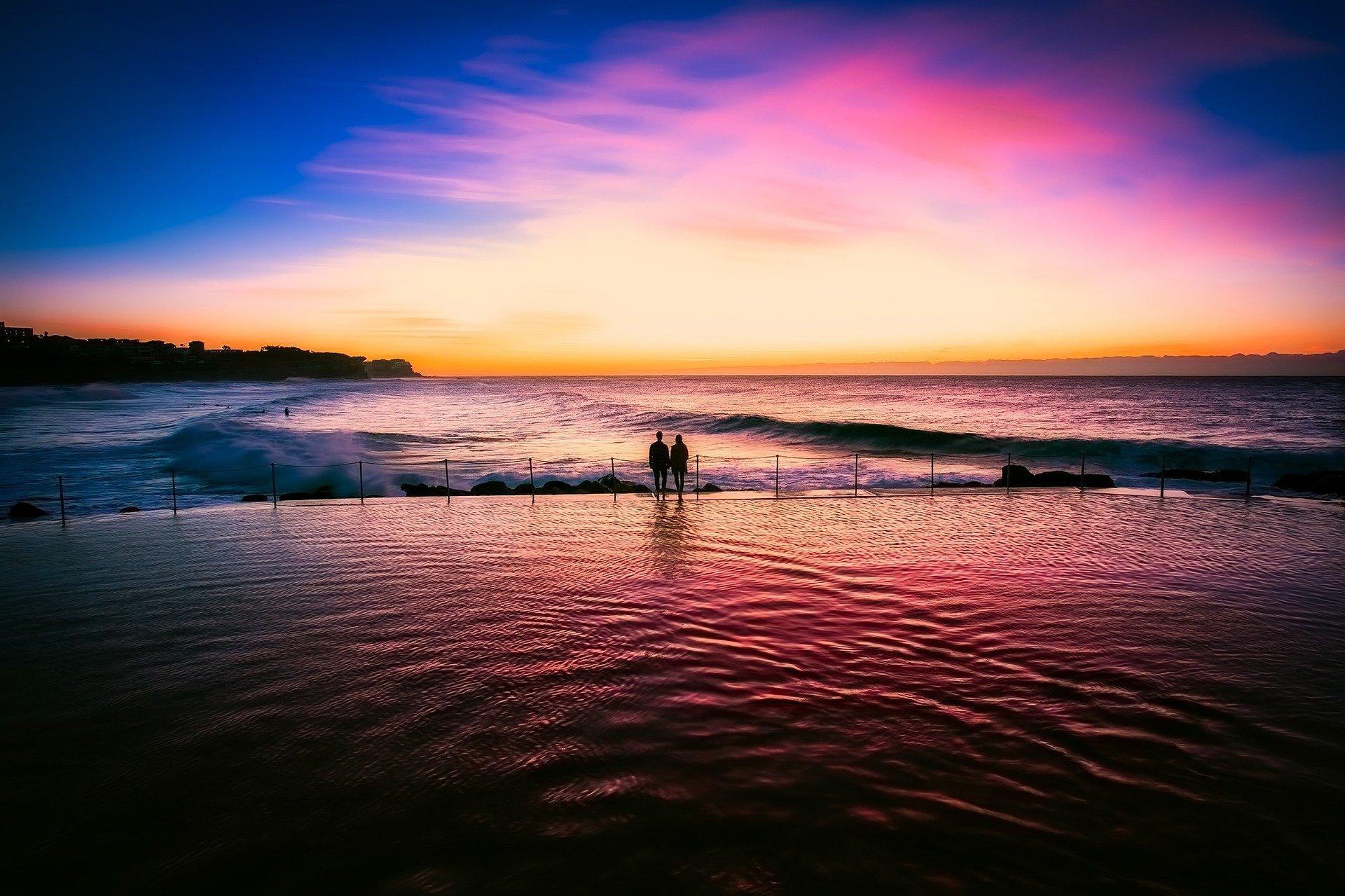 tra le insenature del mare, le ombre di una coppia rivolta al tramonto