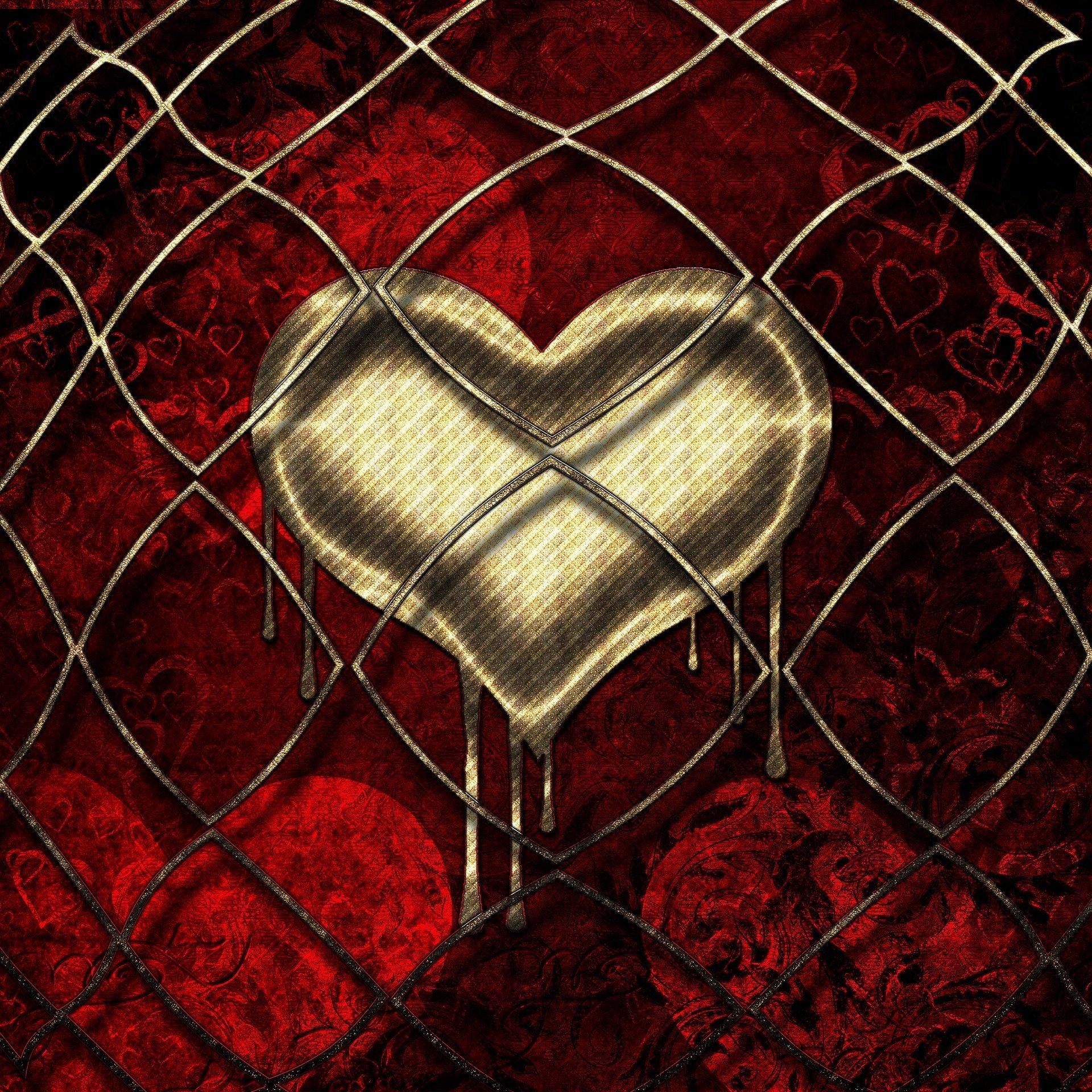 un cuore color oro che si scioglie, su sfondo rosso, dietro una rete metallica