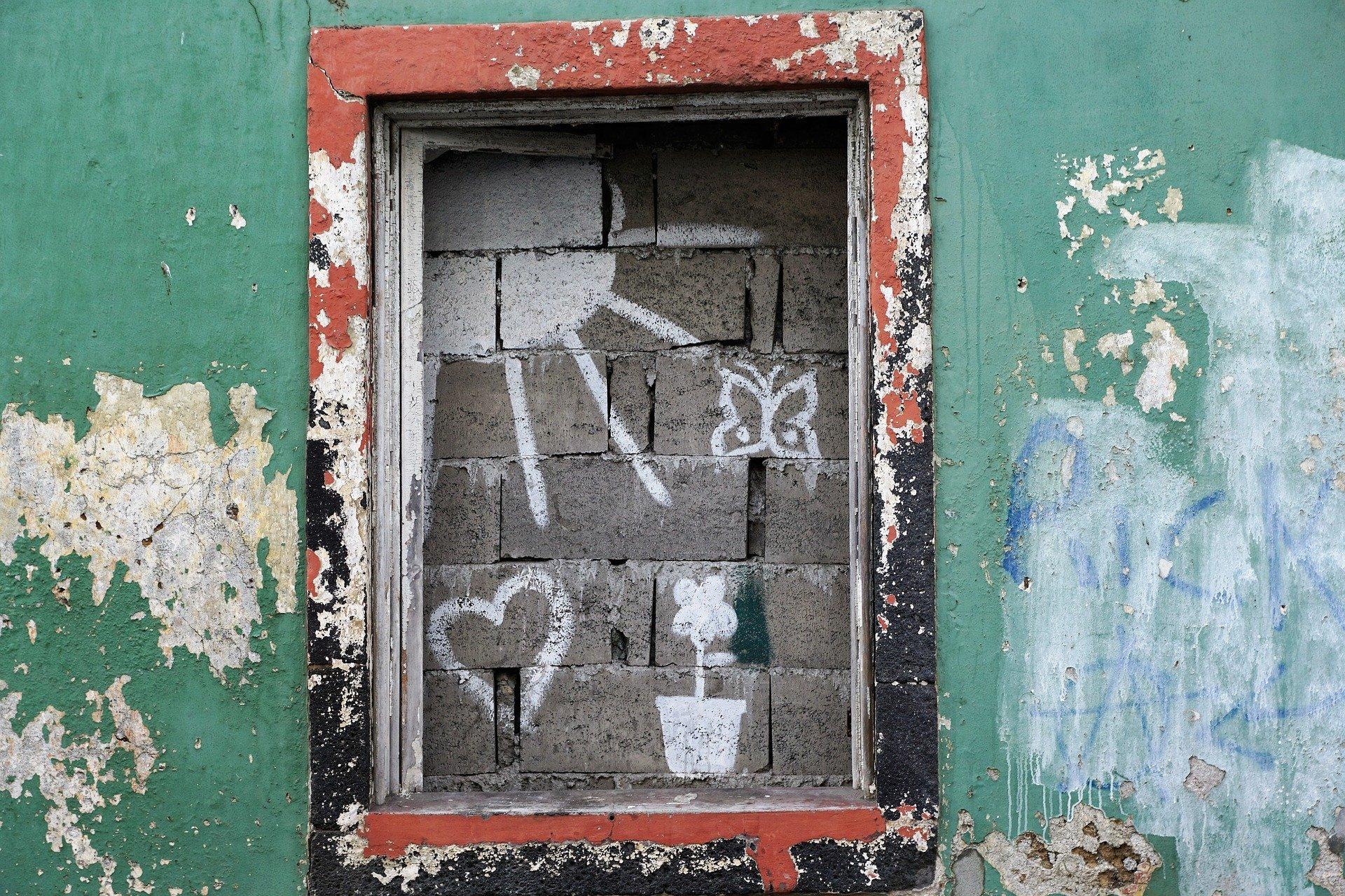 vecchia finestra marrone su parete verde rovinate, finestra cementata con sopra disegnato un cuore, farfalla, fiore e sole