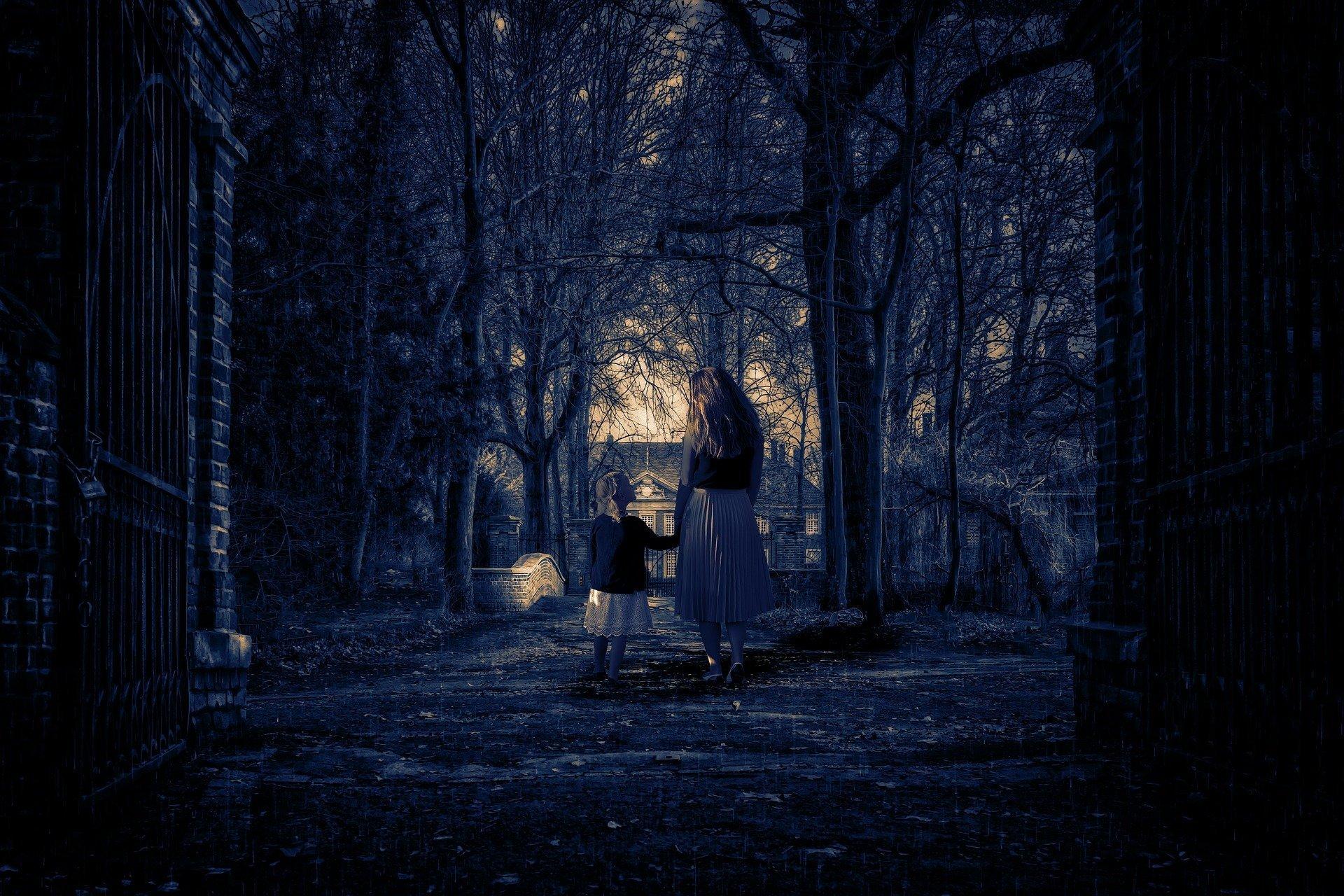 di notte uma donna per mano ad una bambina attraversano un sentiero con alberi andando verso un'abitaizone