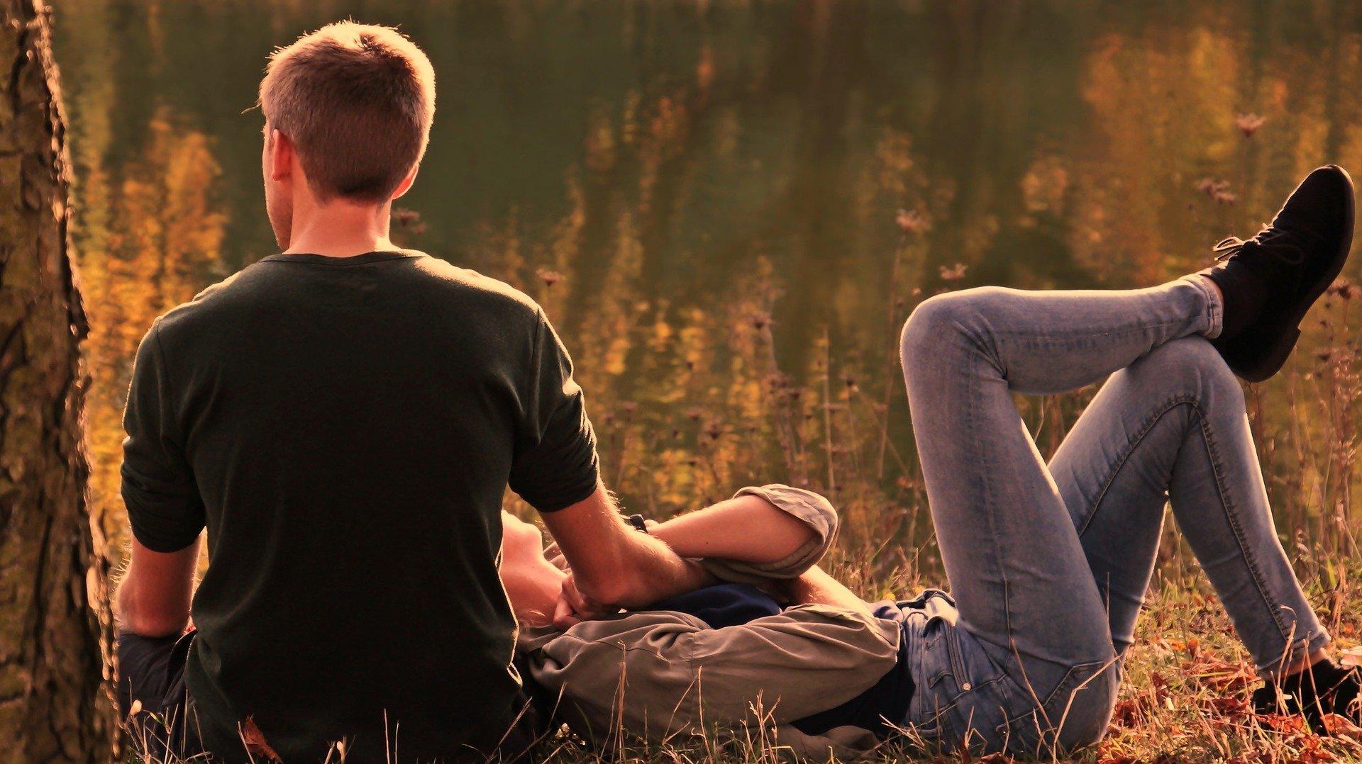 coppia di spalle in un campo, lui seduto e lei sdraiata con la testa sulle sue gambe