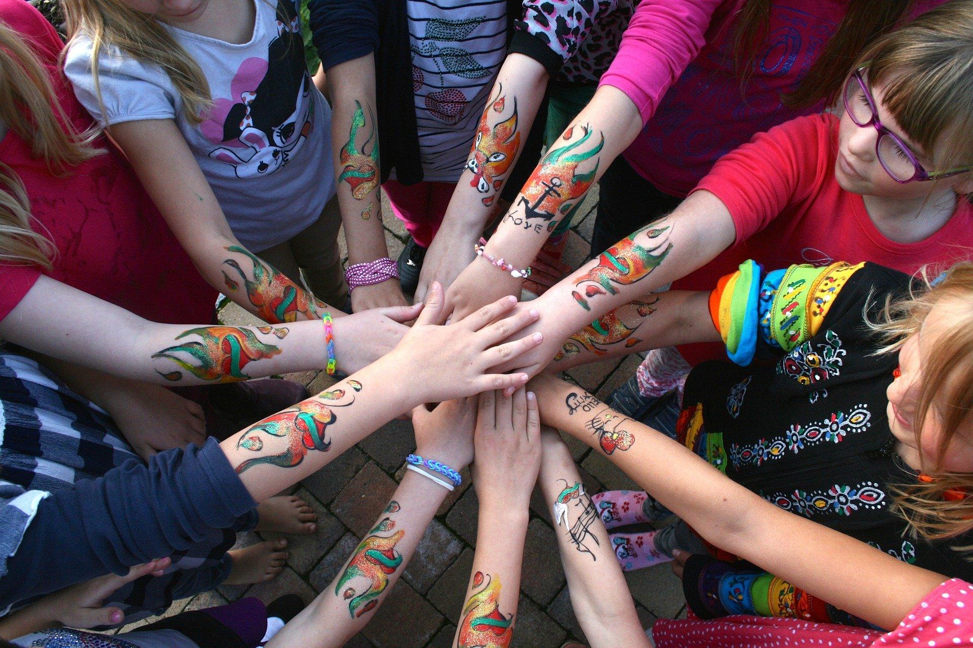 mani unite di ragazzi con tatuaggi colorati al braccio