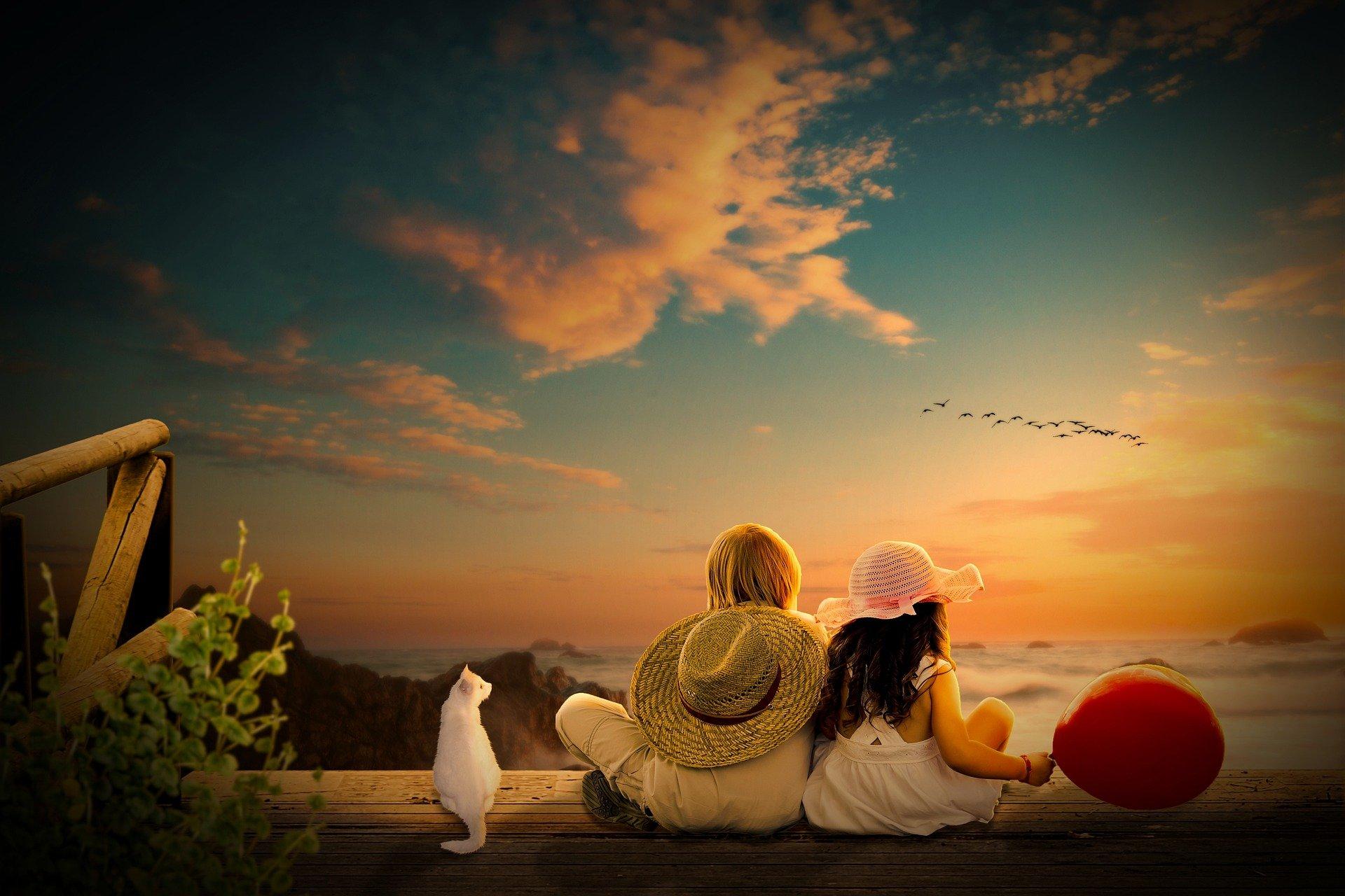 due ragazzi con un cappello, di spalle, con un gatto e un palloncino, che guardano l'orizzonte azzurro e illuminato dal sole
