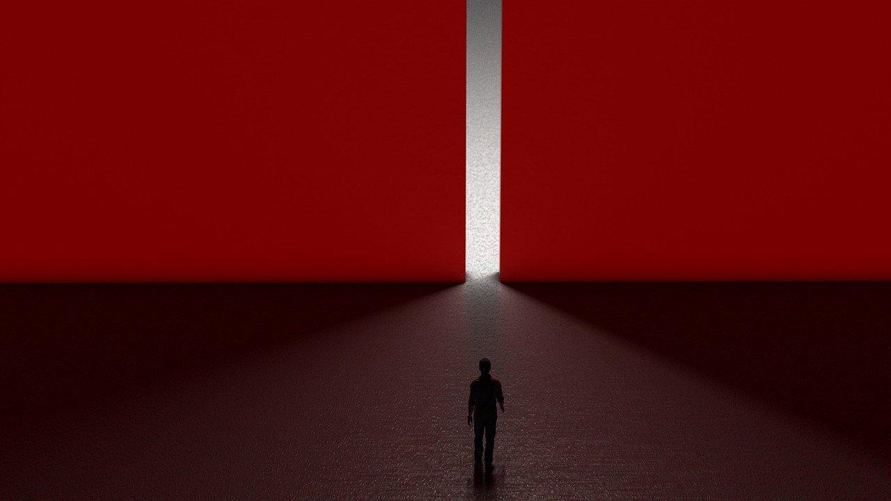 uomo al buio di schiena che va verso una parete rossa gigantesca con uno stretto varco dal quale esce la luce