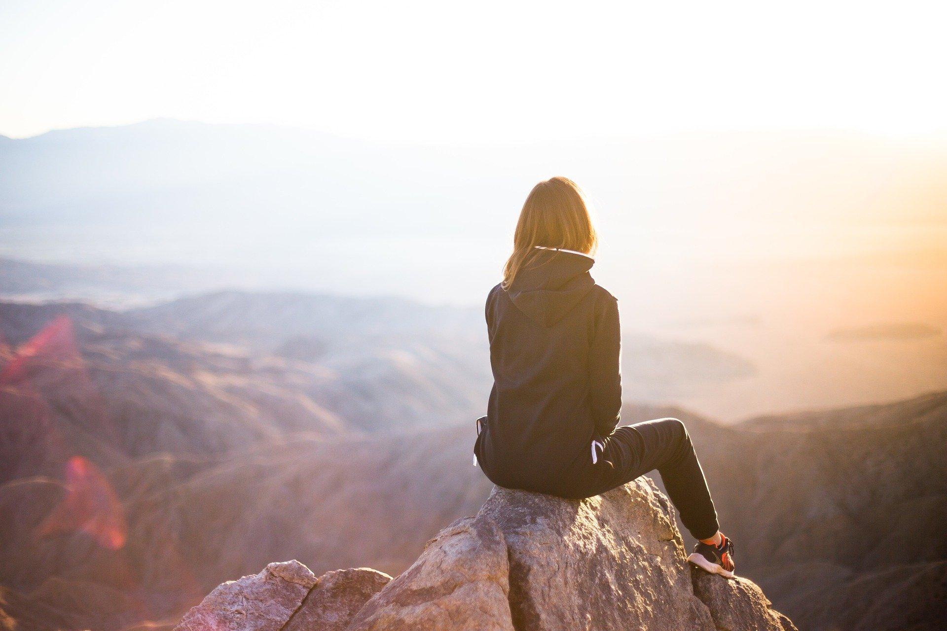 ragazza di spalle sulla cima di una montagna a guardare il sole