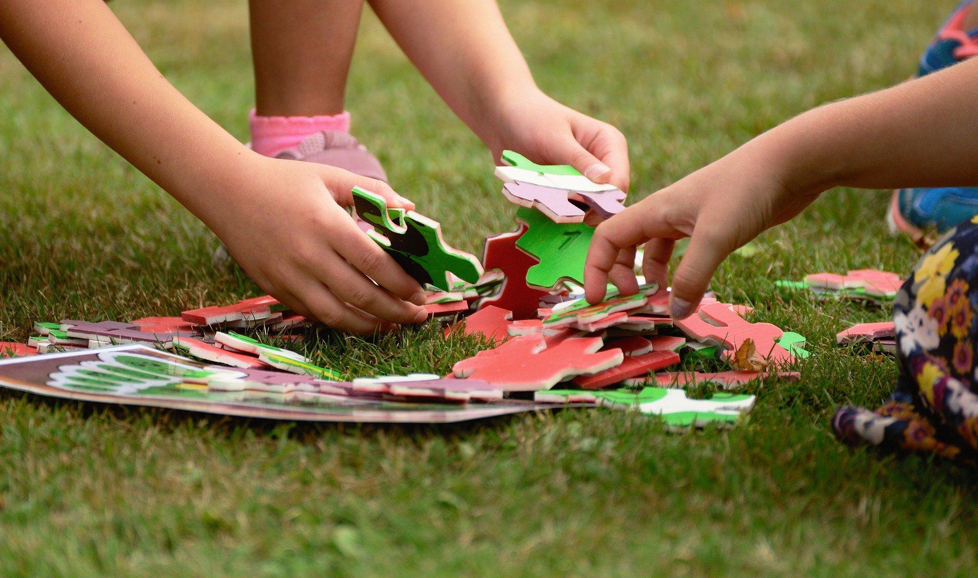 mani di due bambini che sistemano i pezzi di un puzzle
