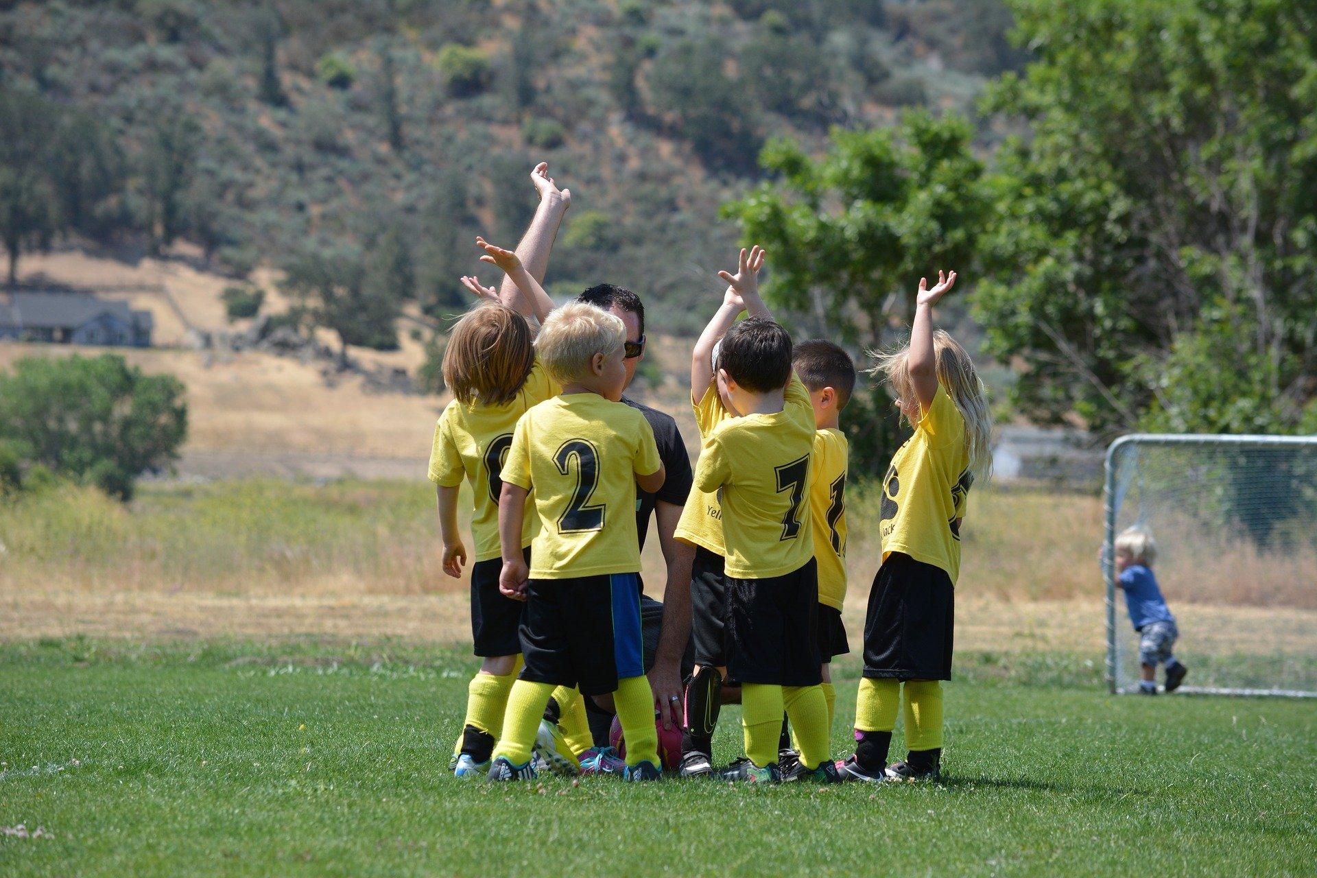 bambini in uniforme che giocano in un parco e che in cerchio si danno il cinque