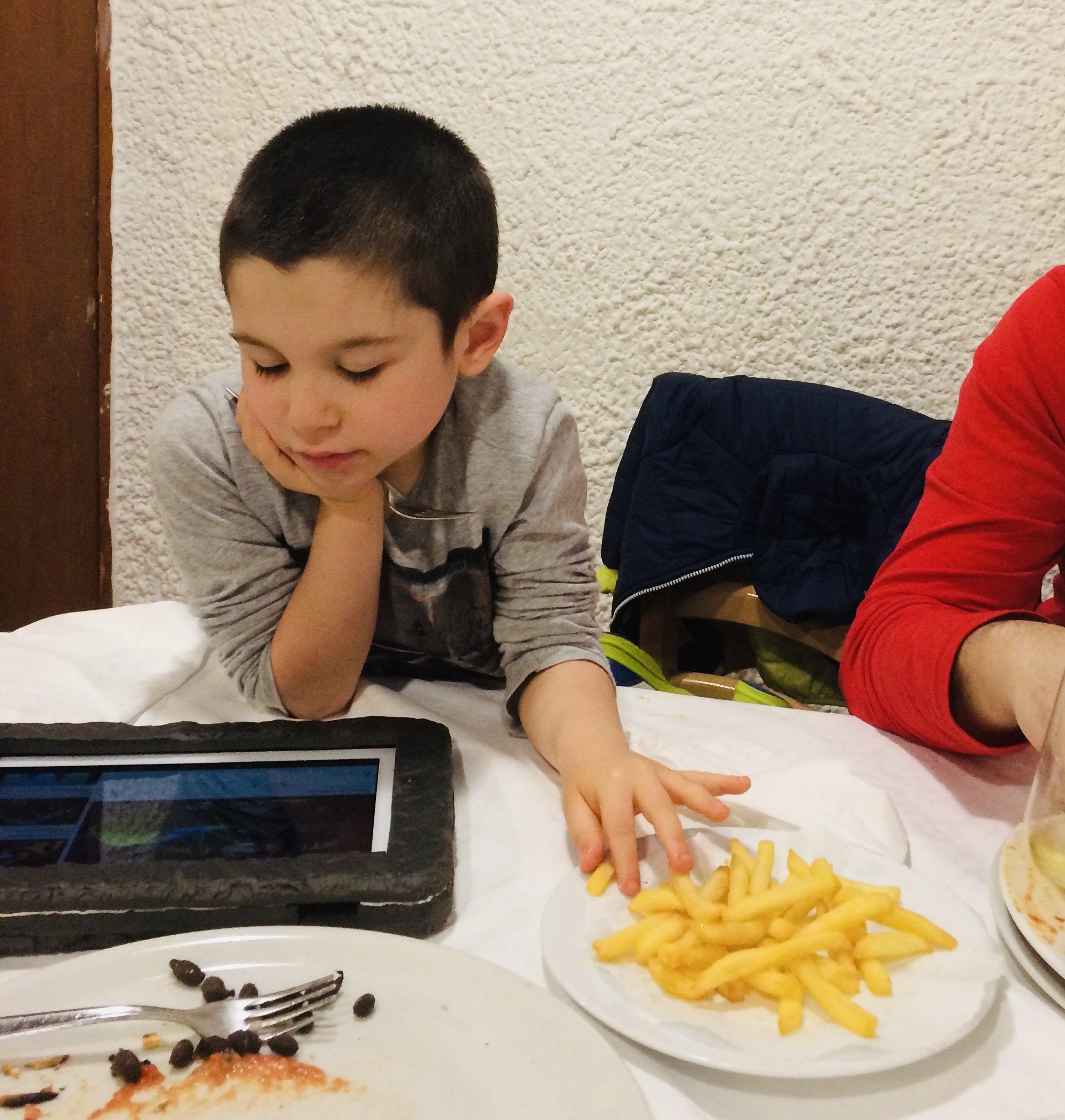 giuliano a tavola al ristorante con patatine e tablet