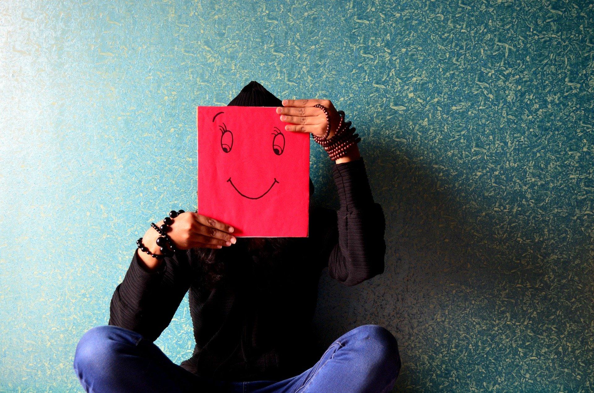 una persona seduta con davanti la faccia un foglio rosso con disegnati occhi e bocca sorridenti
