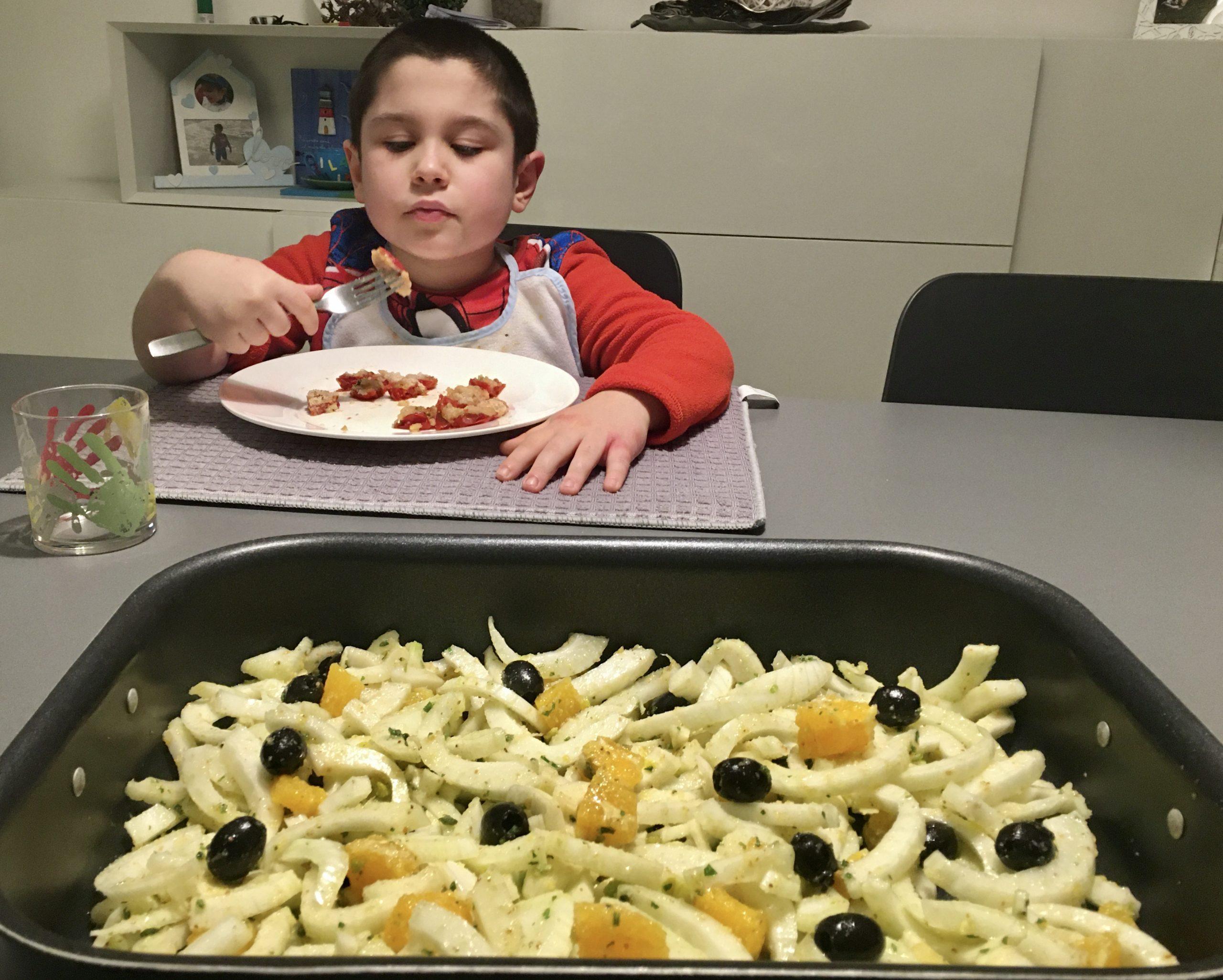 insalata di finocchi in teglia e sullo sfondo Giuliano che mangia la pasta
