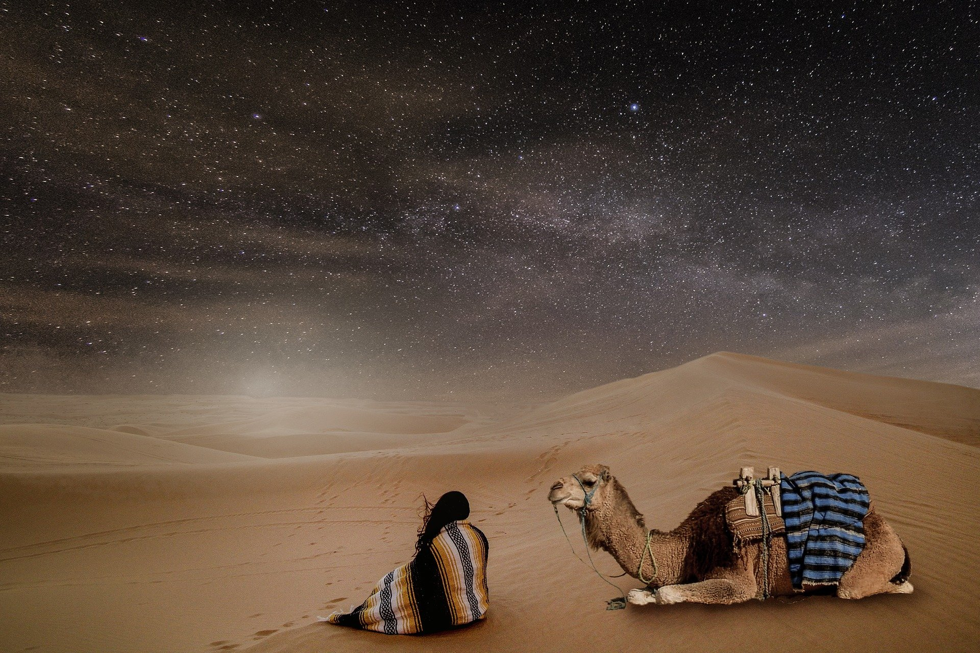 una donna seduta di spalle accanto al suo cammello nel deserto