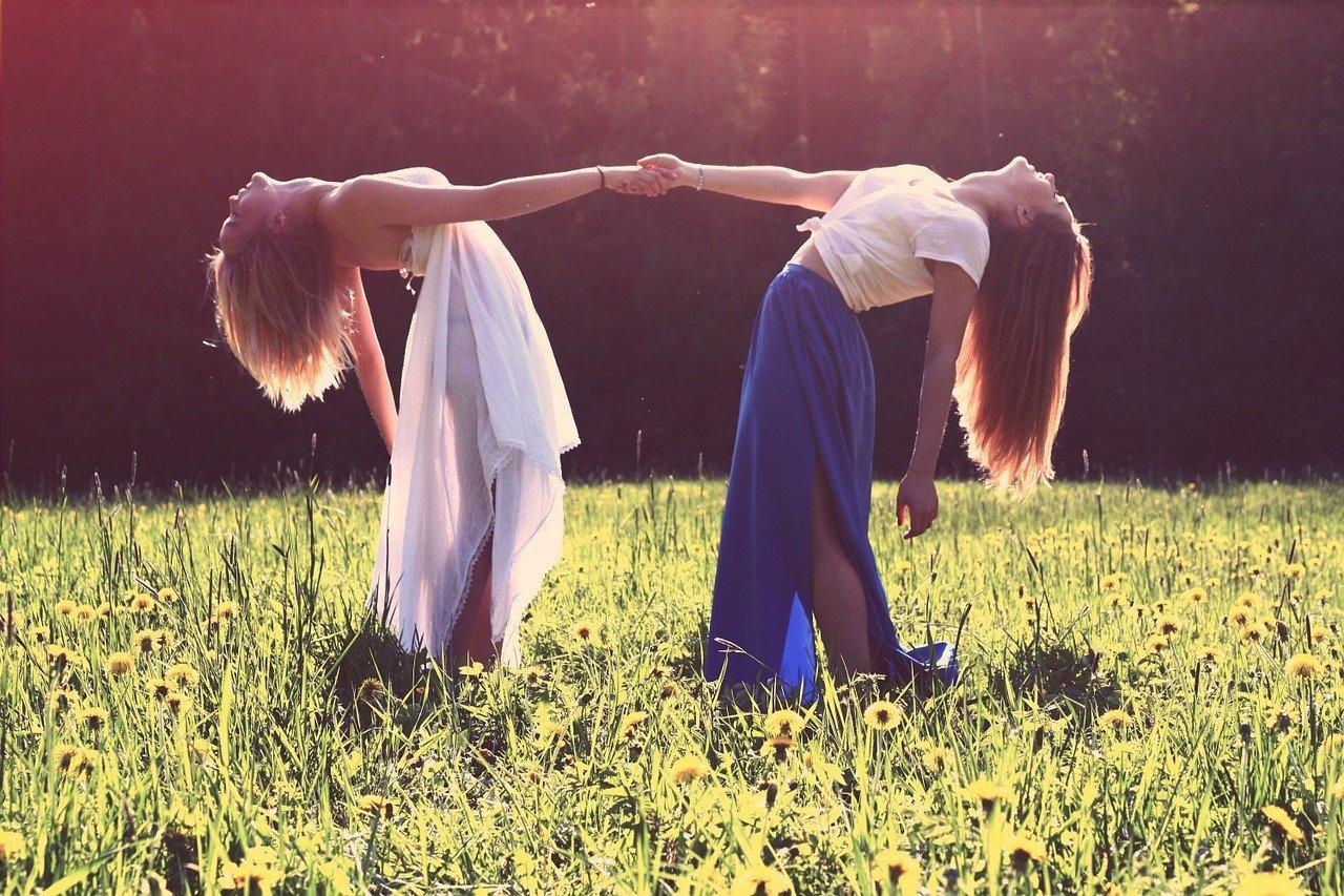 due ragazze che si tengono per mano mentre si buttano all'indietro
