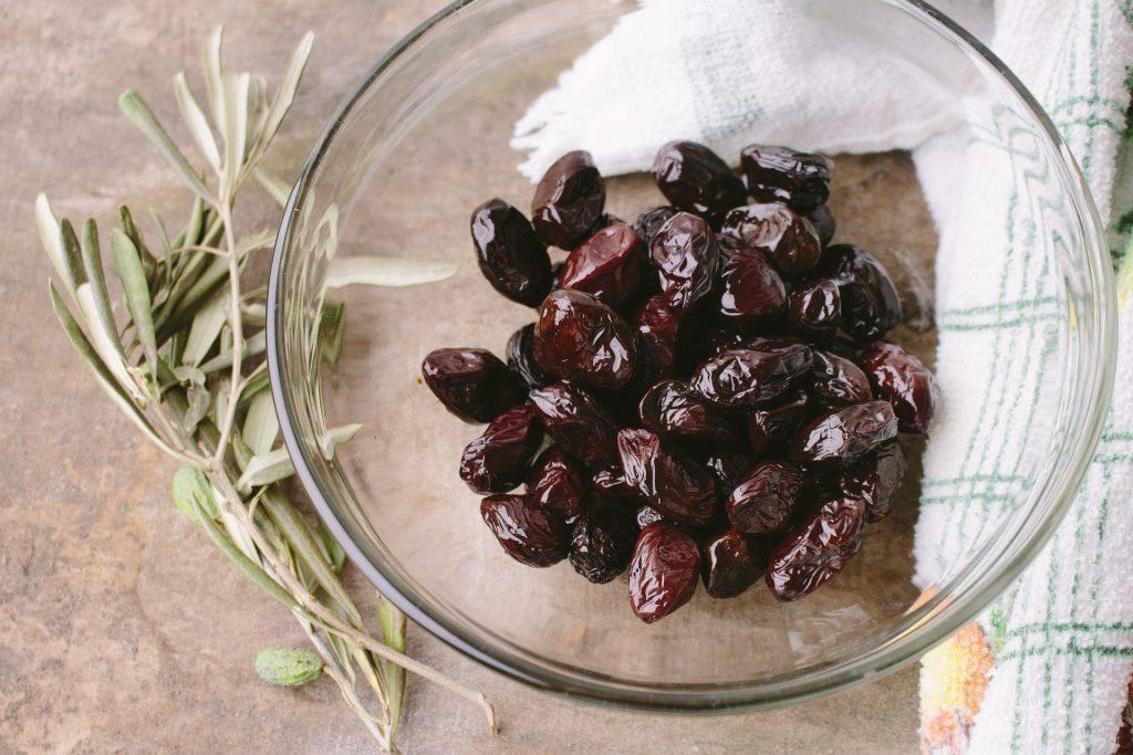 olive taggiasche dentro una ciotola trasparente su un tavolo