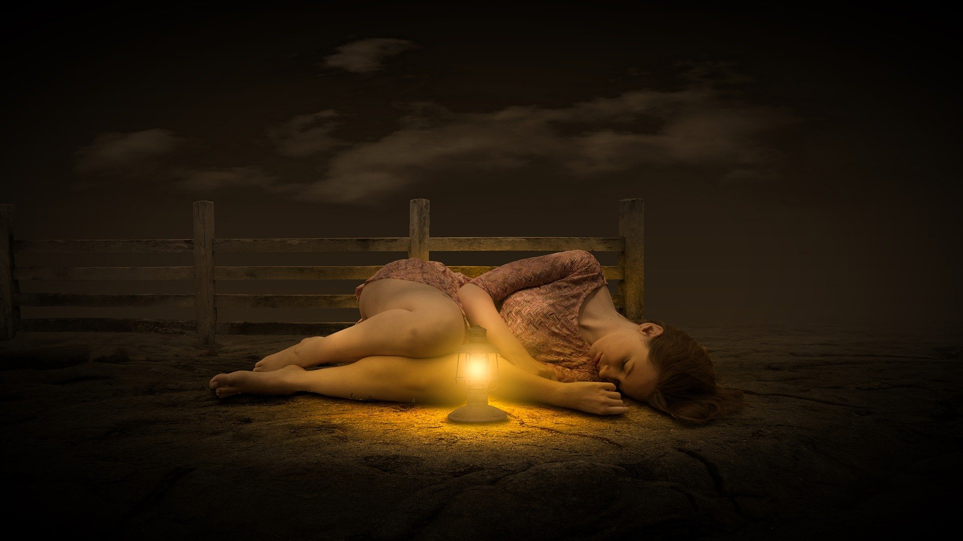 una donna sdraiata a terra rannicchiata su se stessa, di notte, con la luce di una lanterna davanti a sè