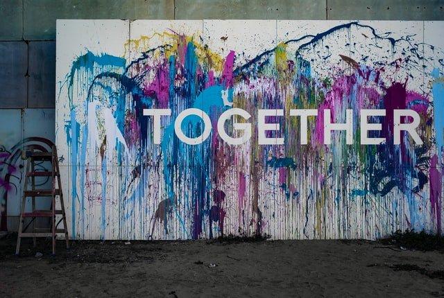 Un murales contiene tanti colori e la parola together, insieme