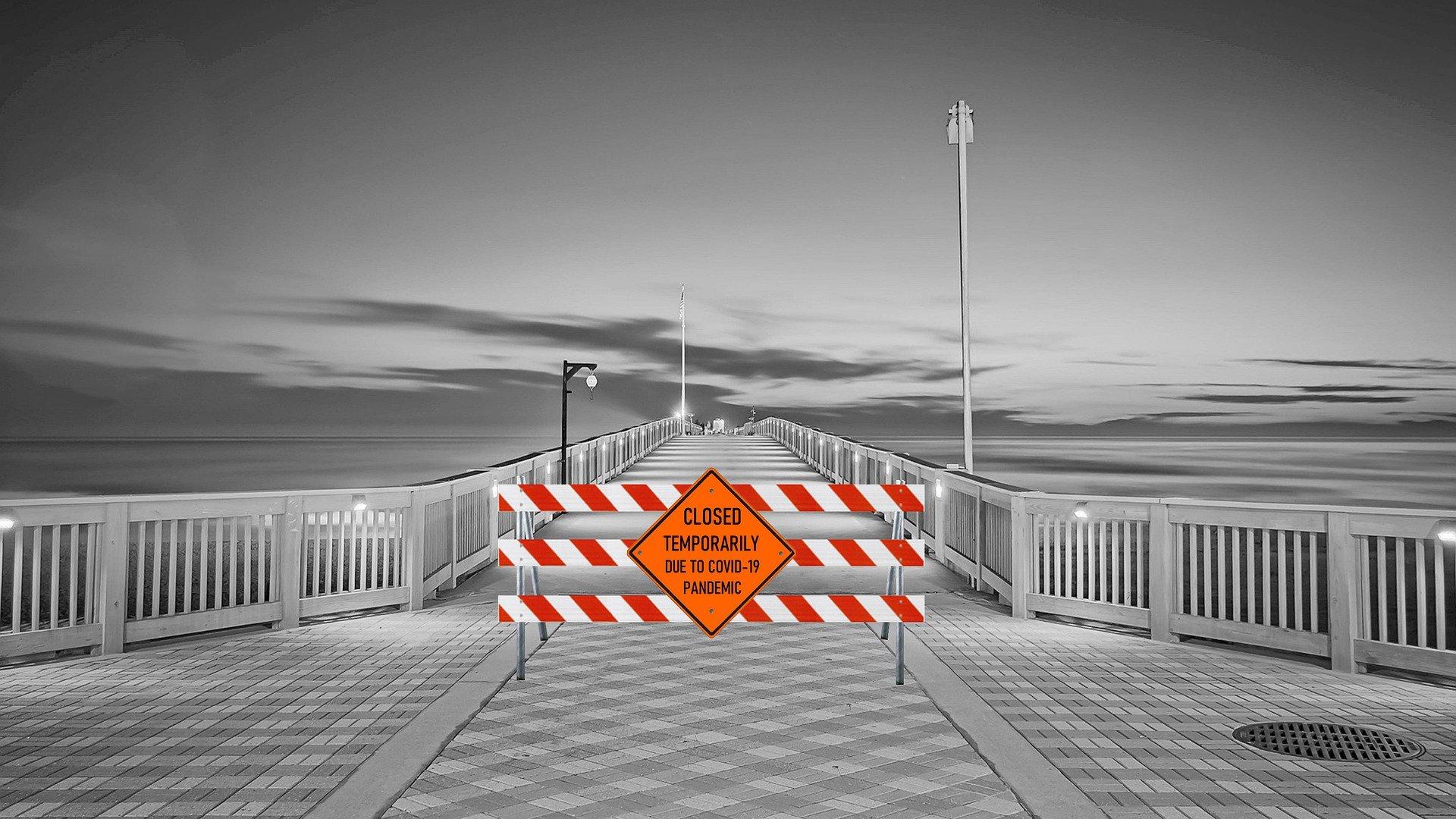 ponte in bianco e nero con una transenna di divieto colorata anti covid