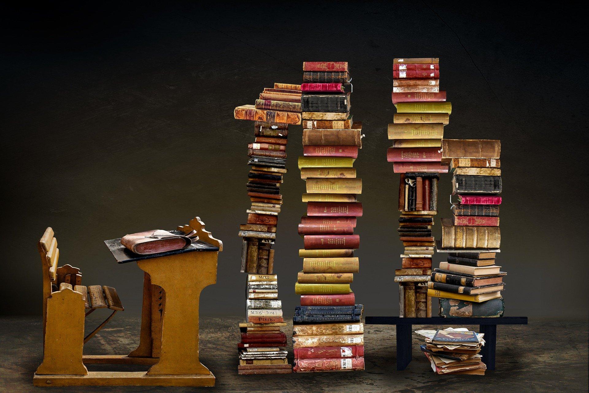 banco di scuola con davanti pile di libri altissime