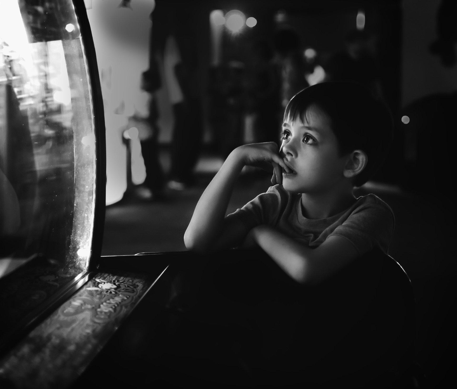 bambino che guarda uno schermo spento