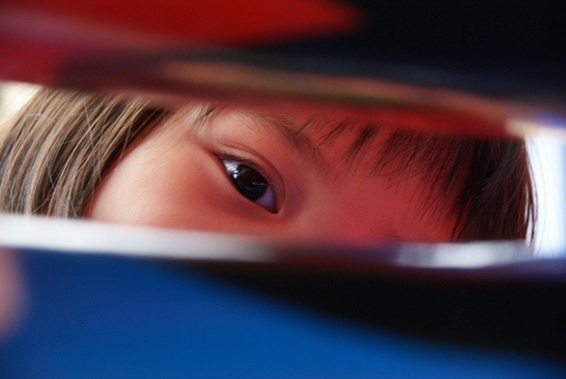parte di viso di una bambina che si intravede da una fessura