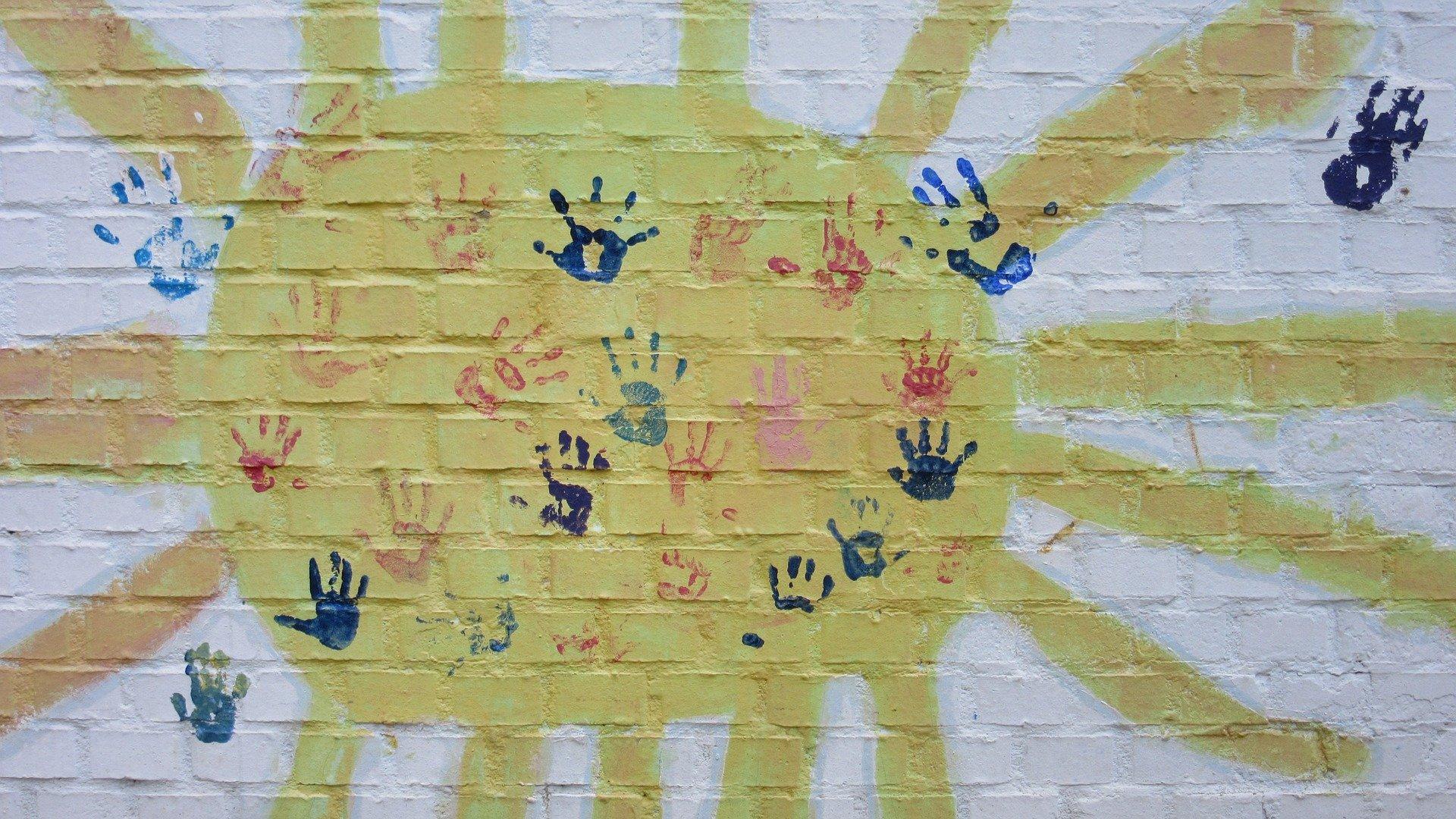 murales raffigurante un sole e impronte colorate di mani