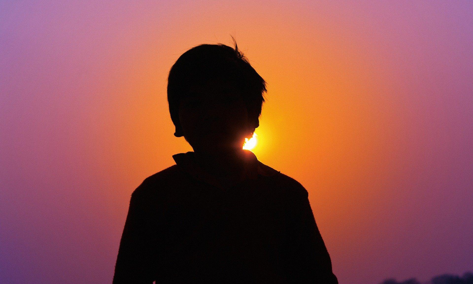 bambino in ombra davanti ad un tramonto