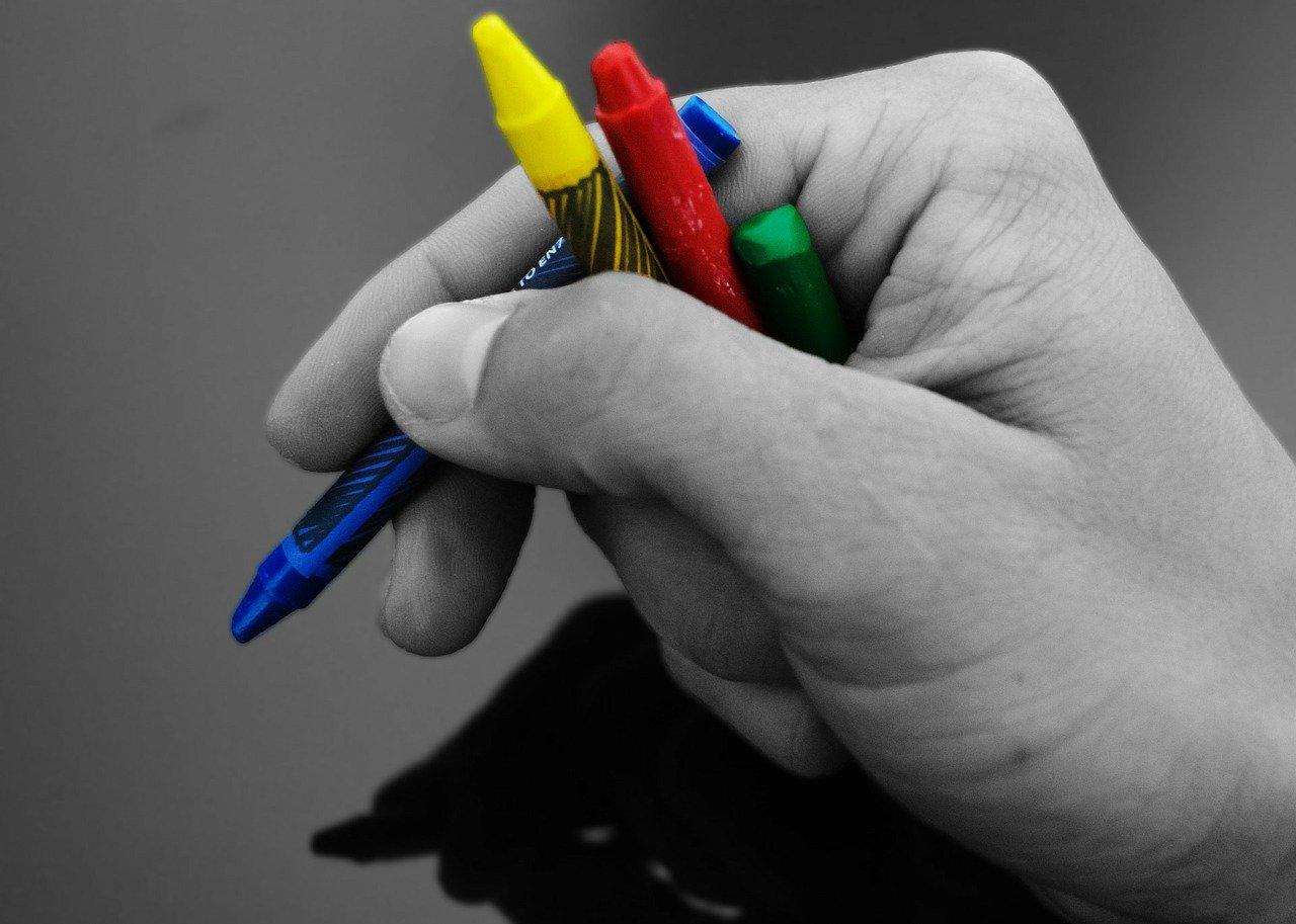 una mano in bianco e nero che stringe colori a cera colorati