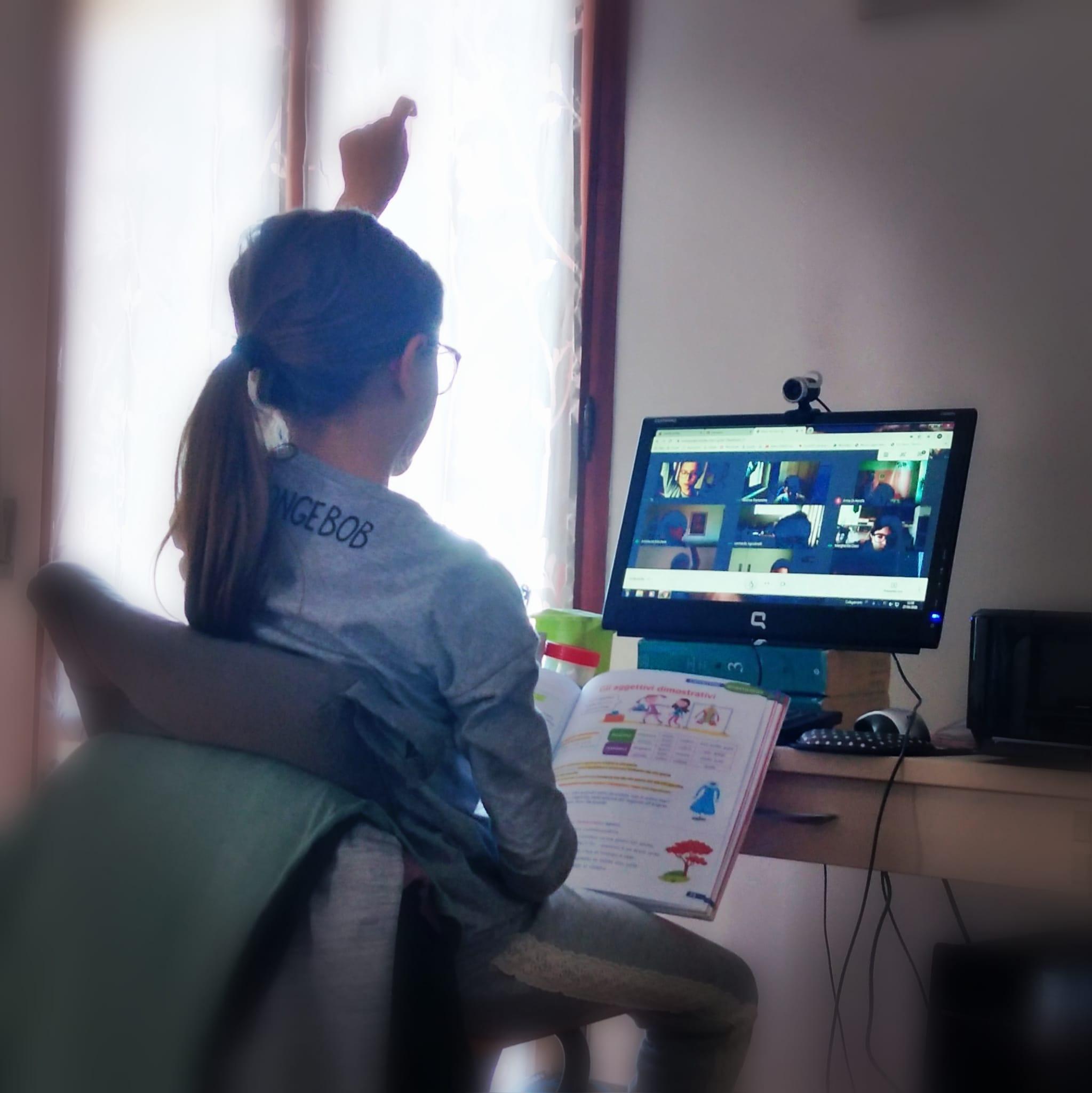 Alice partecipa davanti al computer a una videochiamata di classe ed alza la mano per poter intervenire