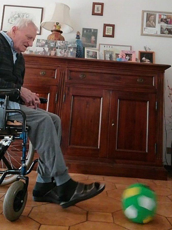 Il bisononno di Alice calcia una palla di stoffa stando in sedia a rotelle