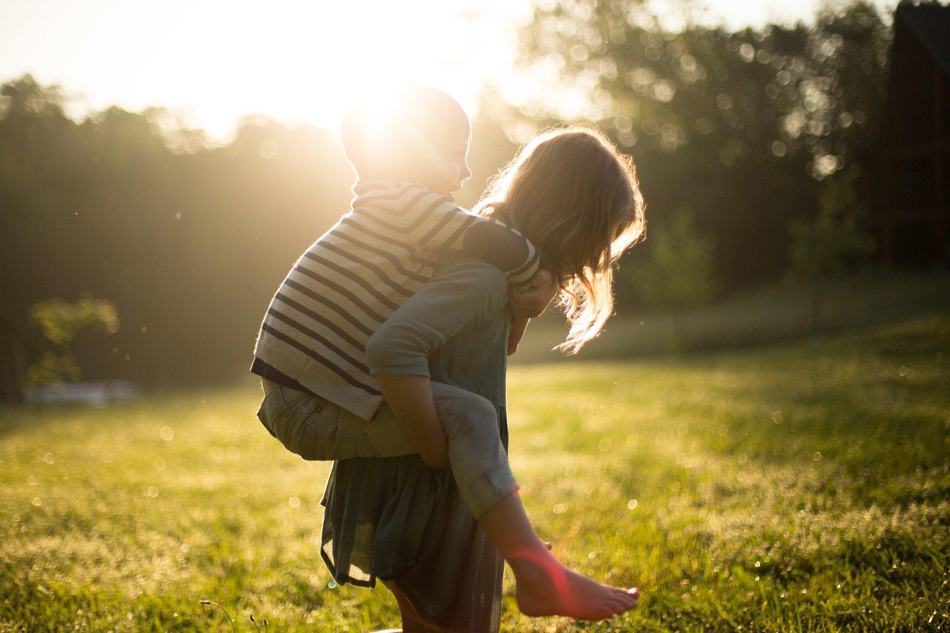 una mamma porta a cavalcioni il proprio bambino in un parco