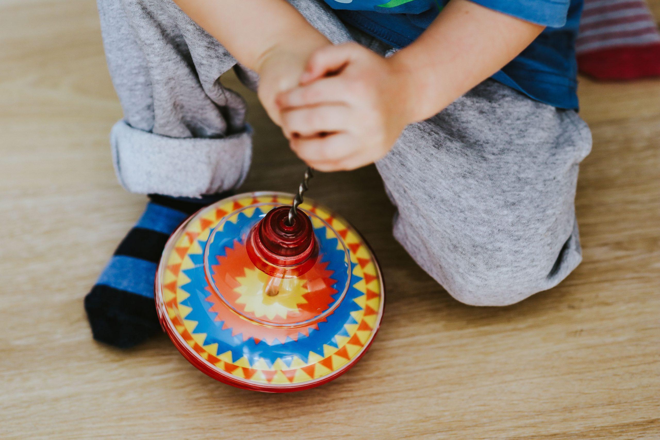 bambino seduto a terra che gioca con una trottola