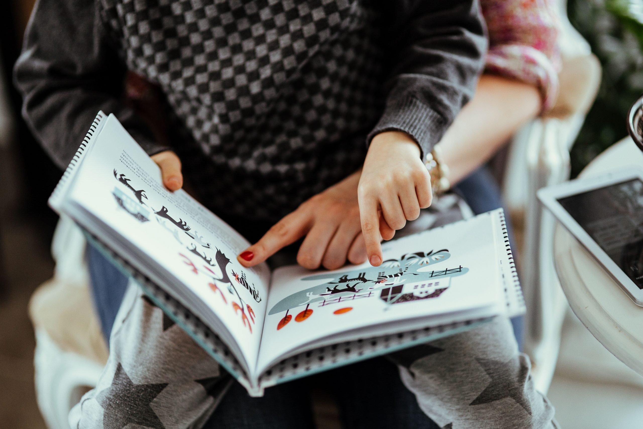 un bambino seduto sulle gambe di una donna mentre guardano un libro