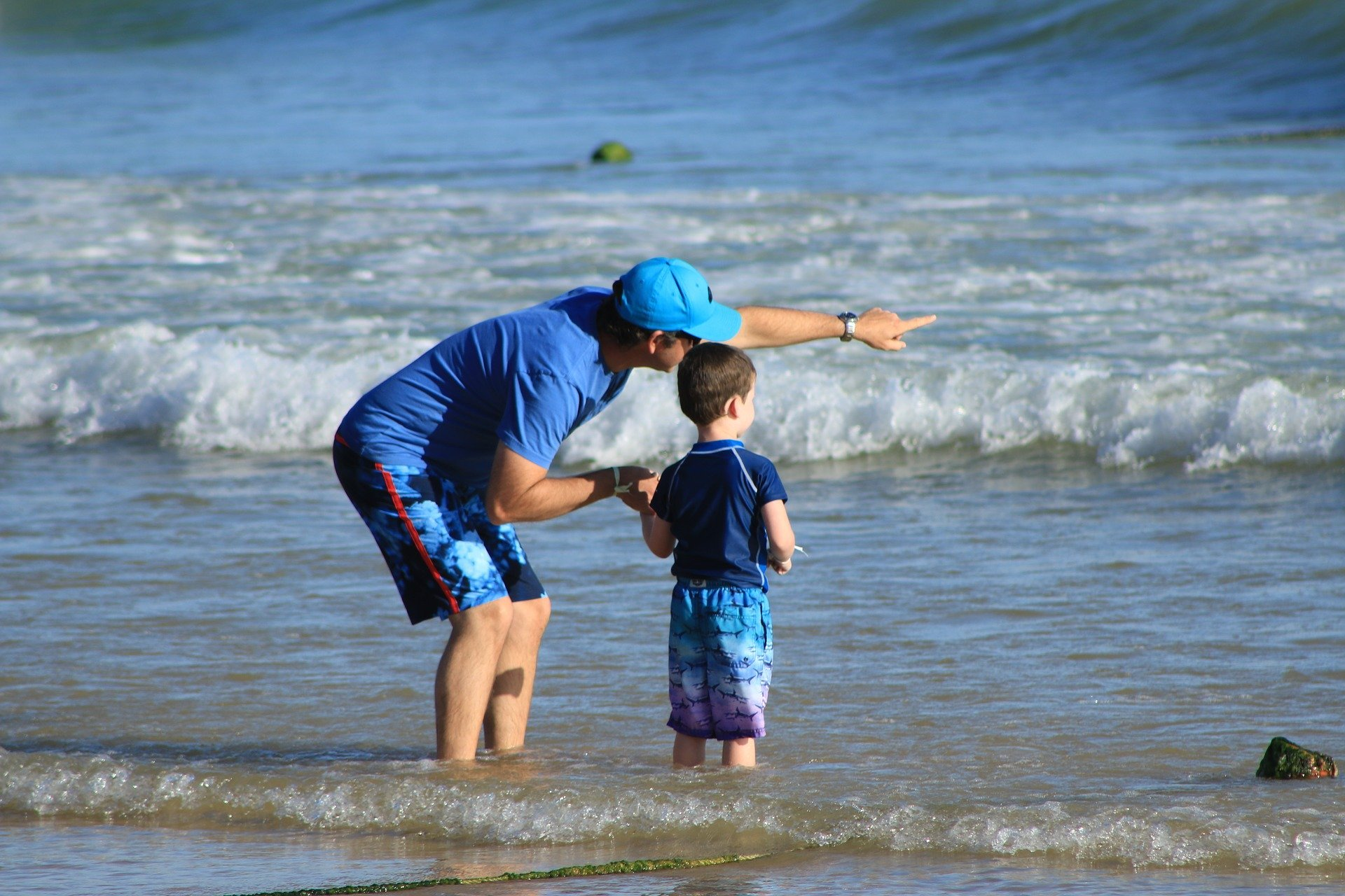 un uomo indica con la mano un punto lontano al figlio mentre sono in riva al mare