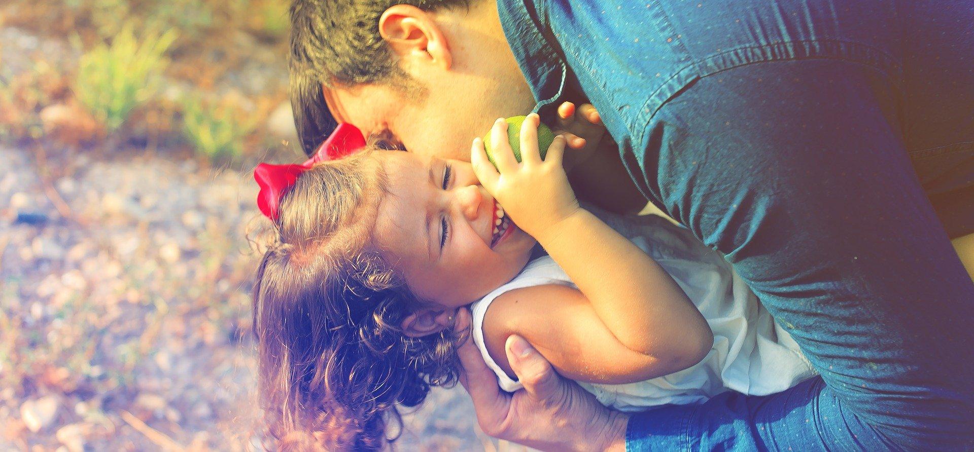 un papà bacia la sua bambina e l'abbraccia mentre ride