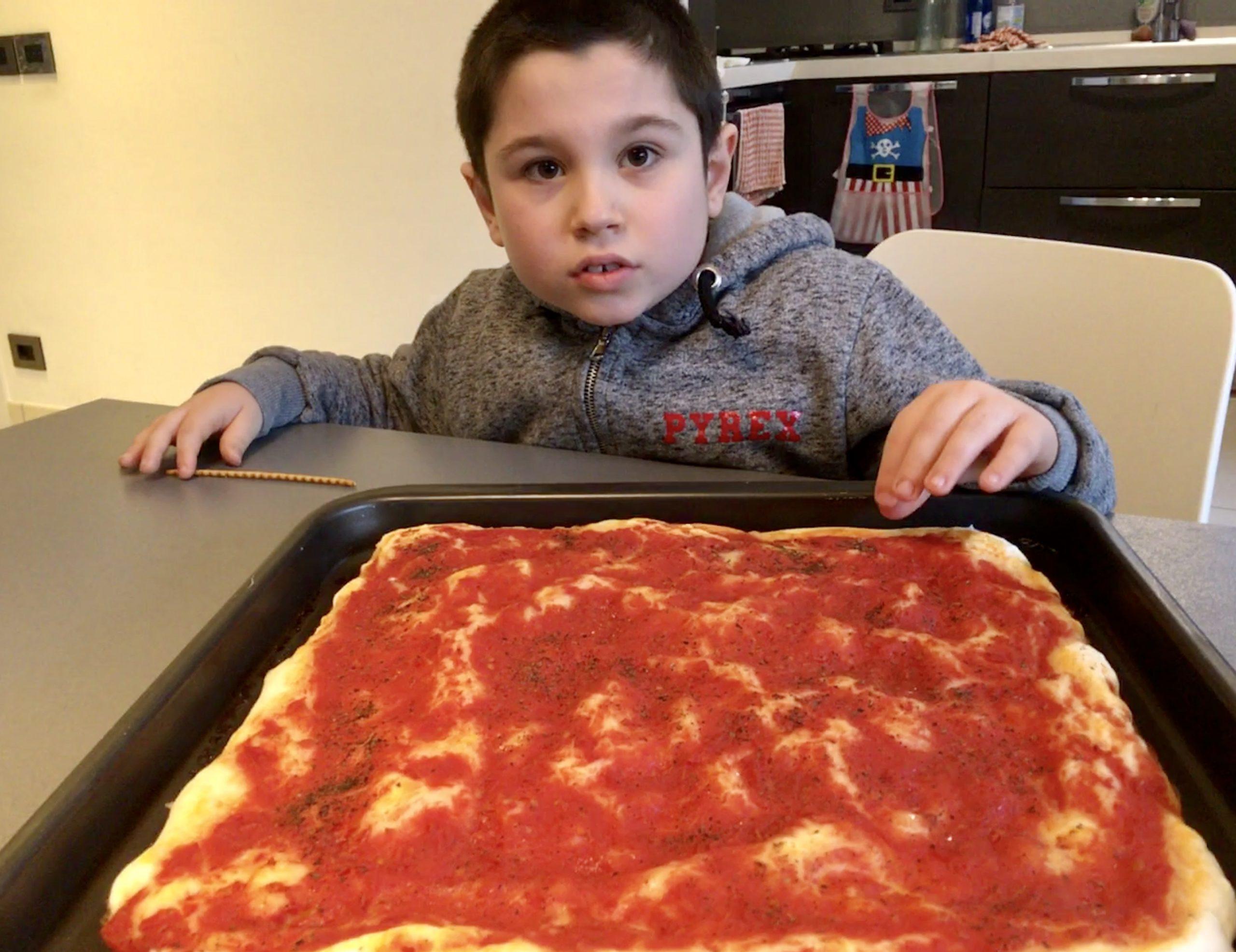 Giuliano davanti ad una teglia di pizza al pomodoro