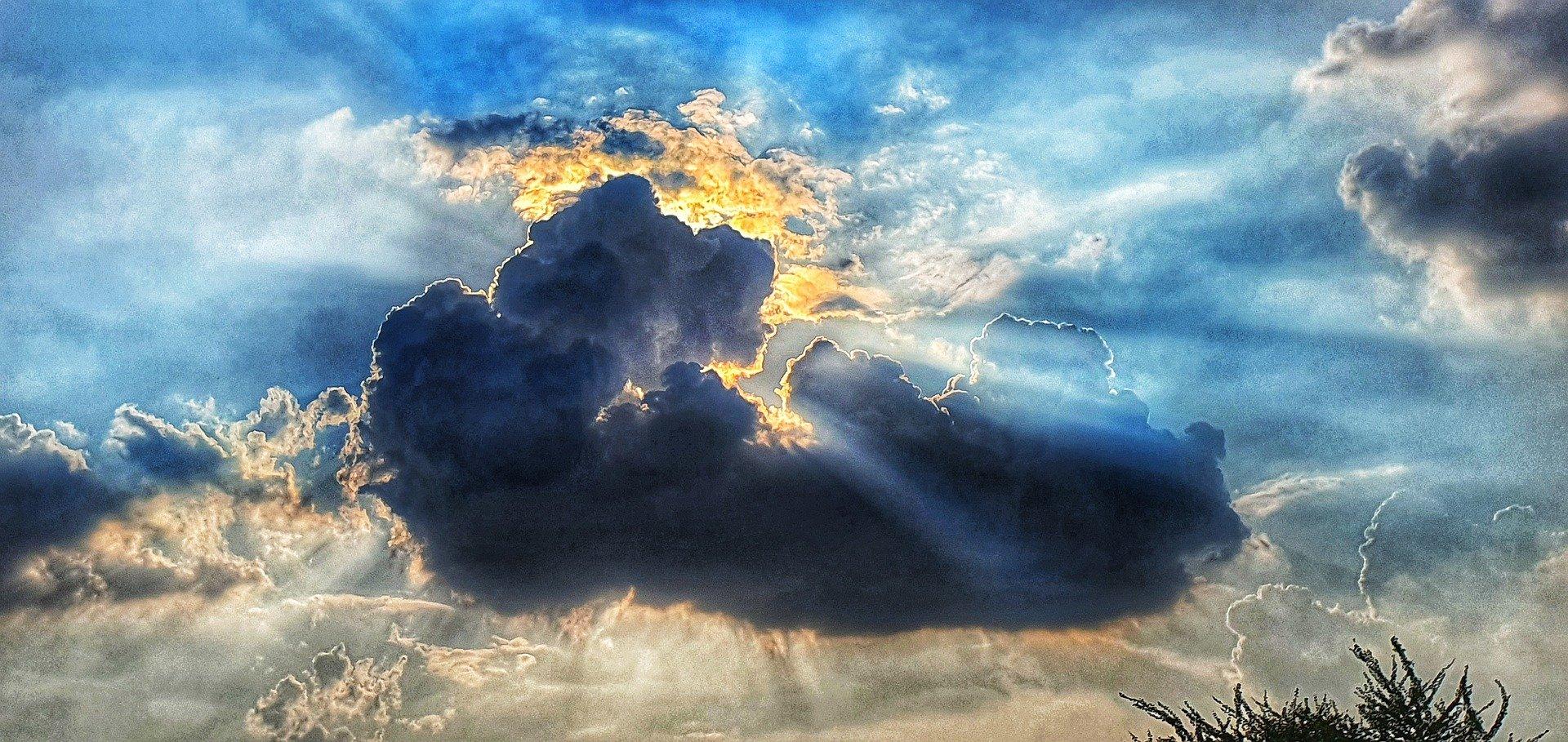 il sole che splende da dietro nuvole nere che si diradano