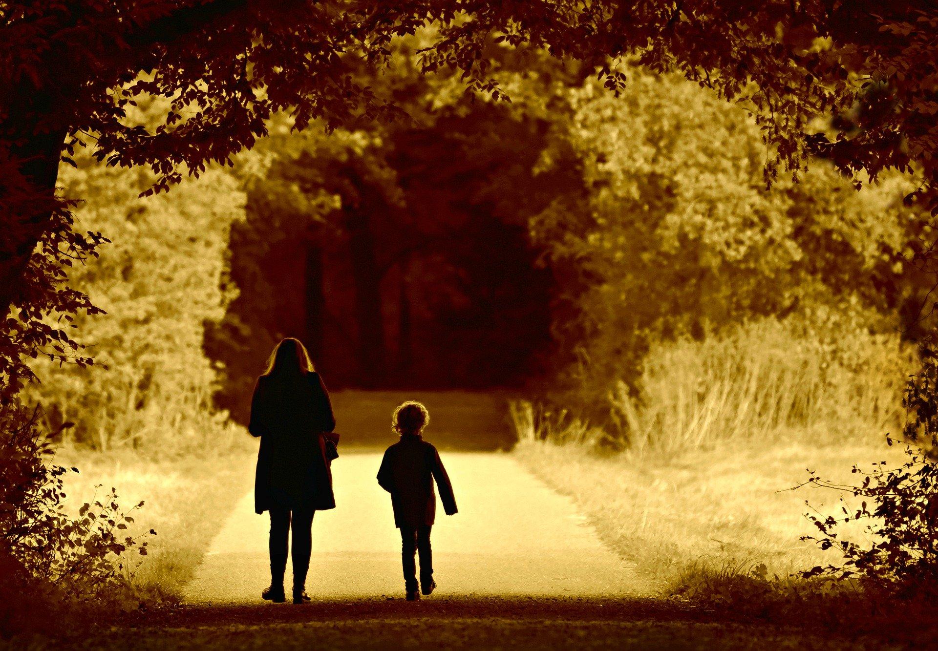 una donna ed un bambino di spalle mentre camminano in una strada circondata da piante
