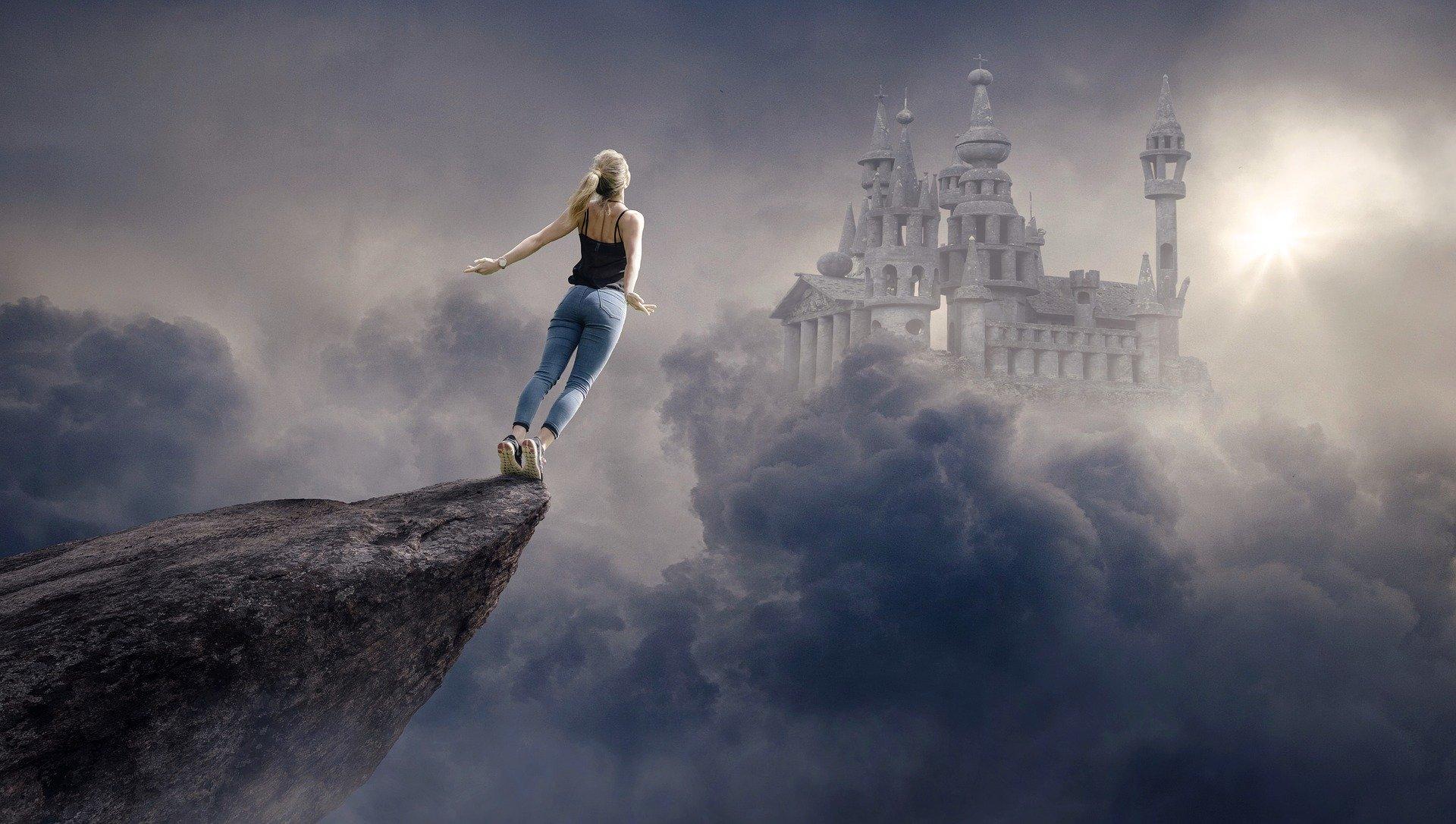 una ragazza di spalle che si butta libera su un precipizio e all'orizzonte un castello tra la nebbia