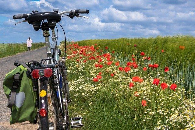 Una donna scesa dalla sua bici si concede una passeggiata solitaria in campagna