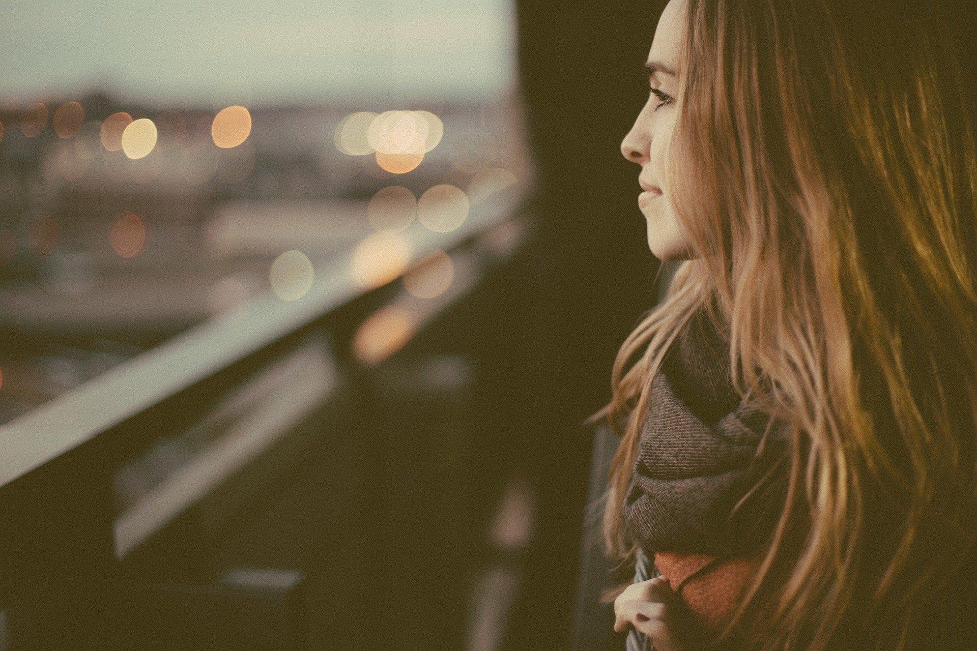 una donna dai capelli lunghi di profilo guarda la città oltre un balcone sorridente