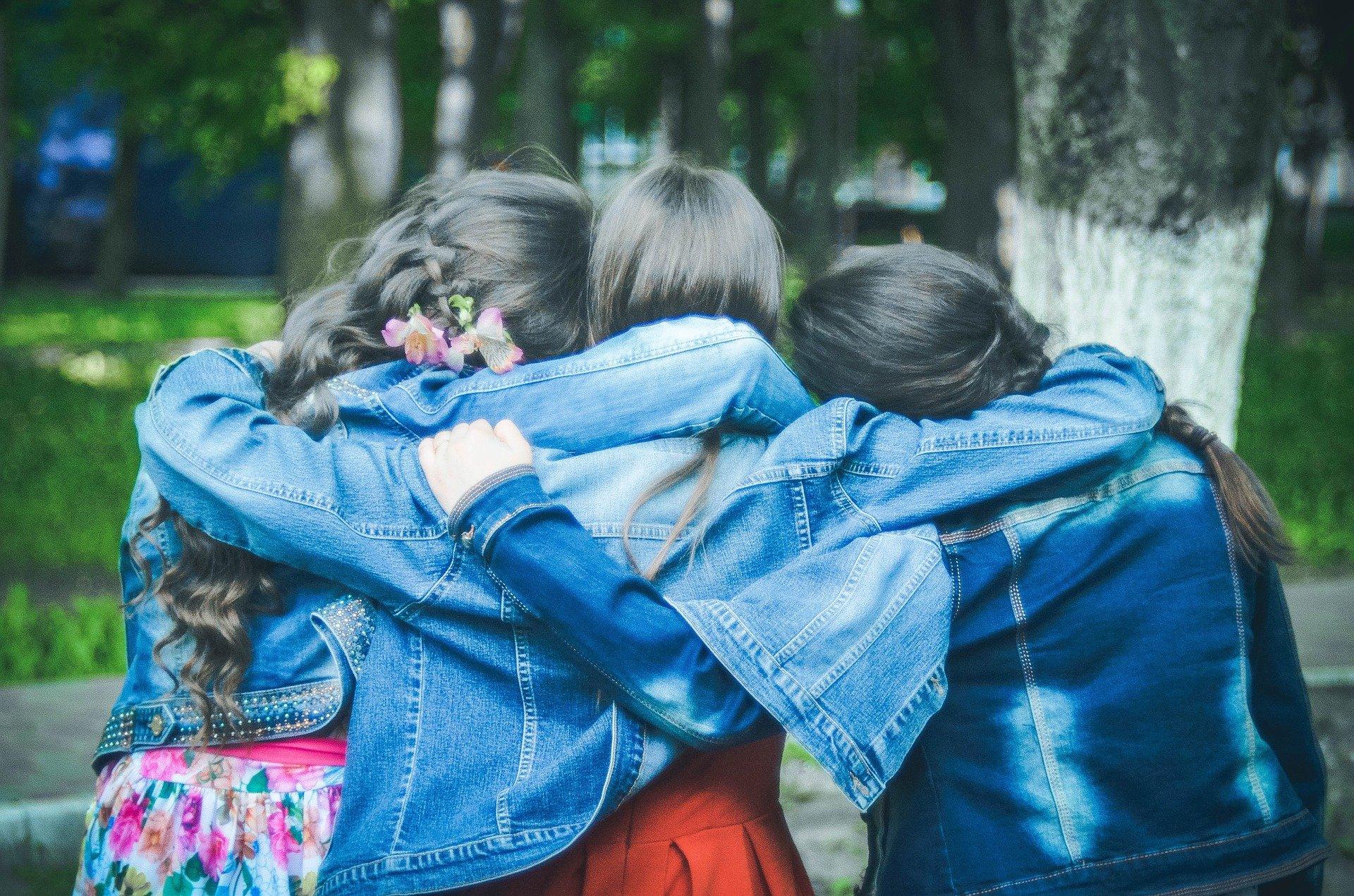 tre ragazze di spalle che si abbracciano