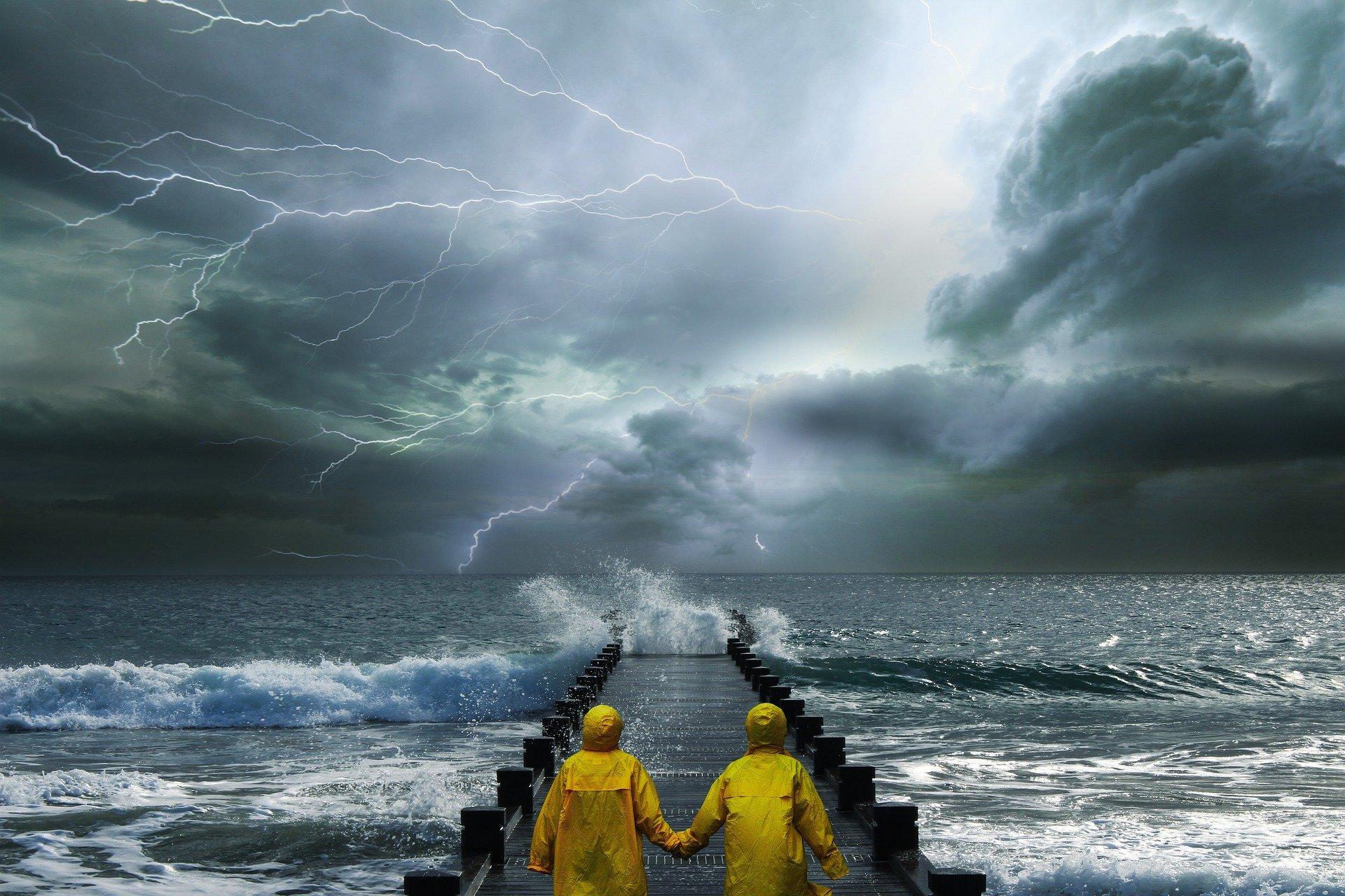 su un pontile durante una tempesta due persone con impermeabile giallo si tengono per mano